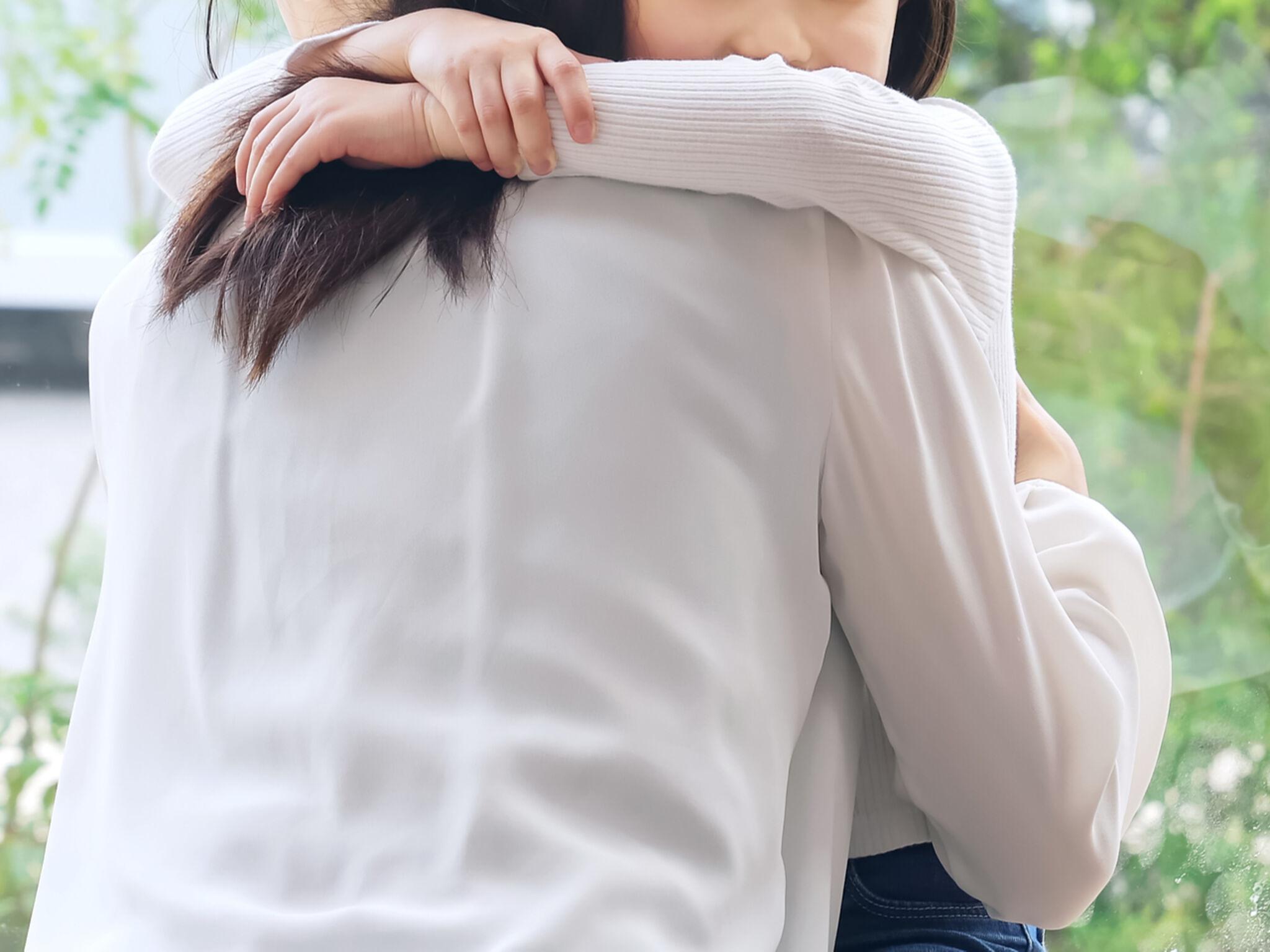 女の子が母親に抱きついている画像