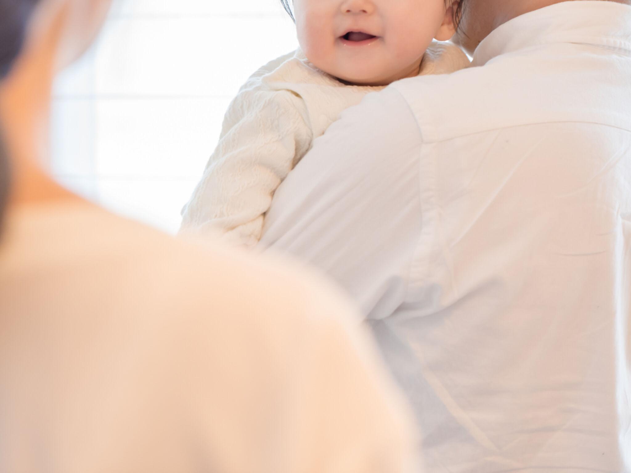 子どもを抱いている父親を見ている母親の画像