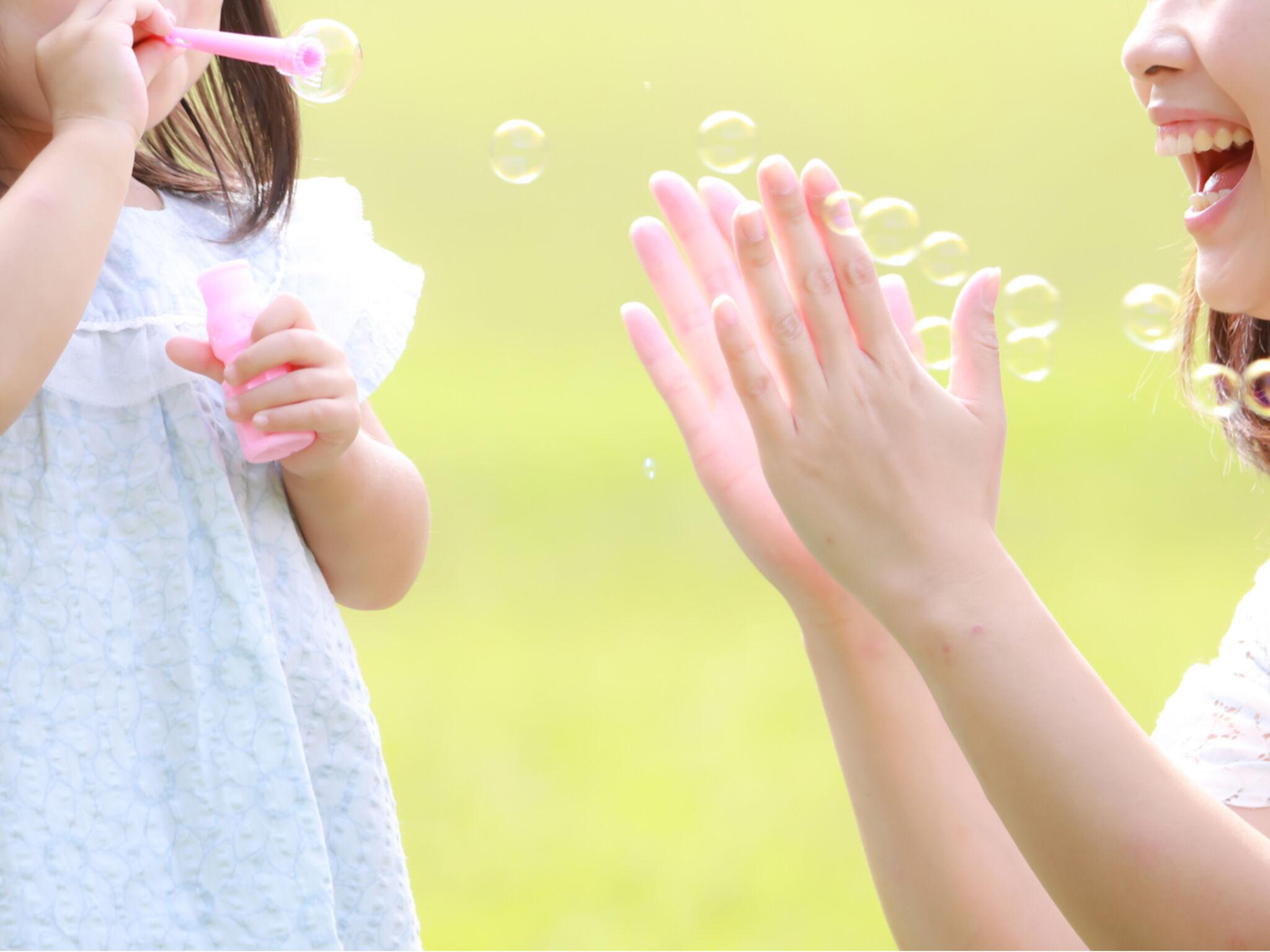 母親と子供がシャボン玉で遊ぶ画像