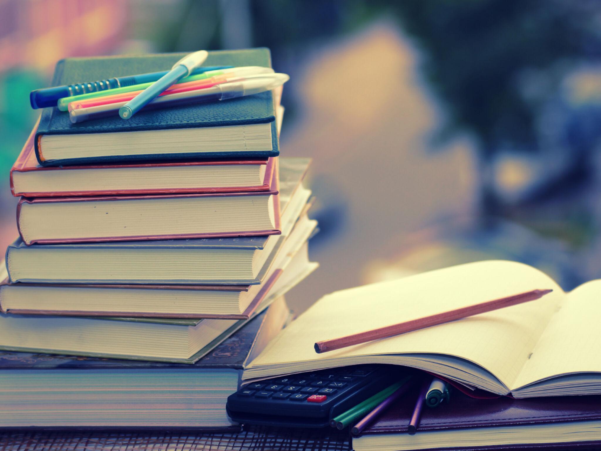詰まれた本とノート、ペンの画像