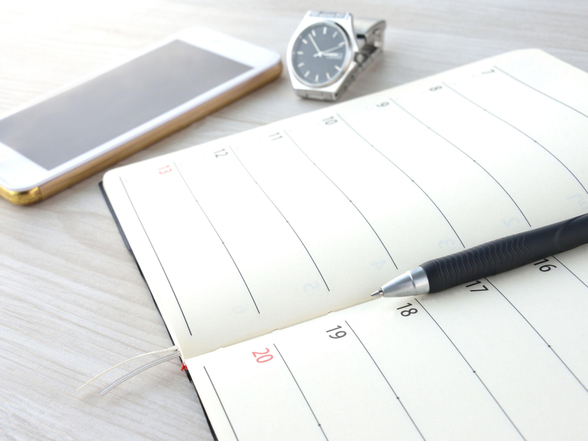 スマートフォンとスケジュール帳と腕時計の画像