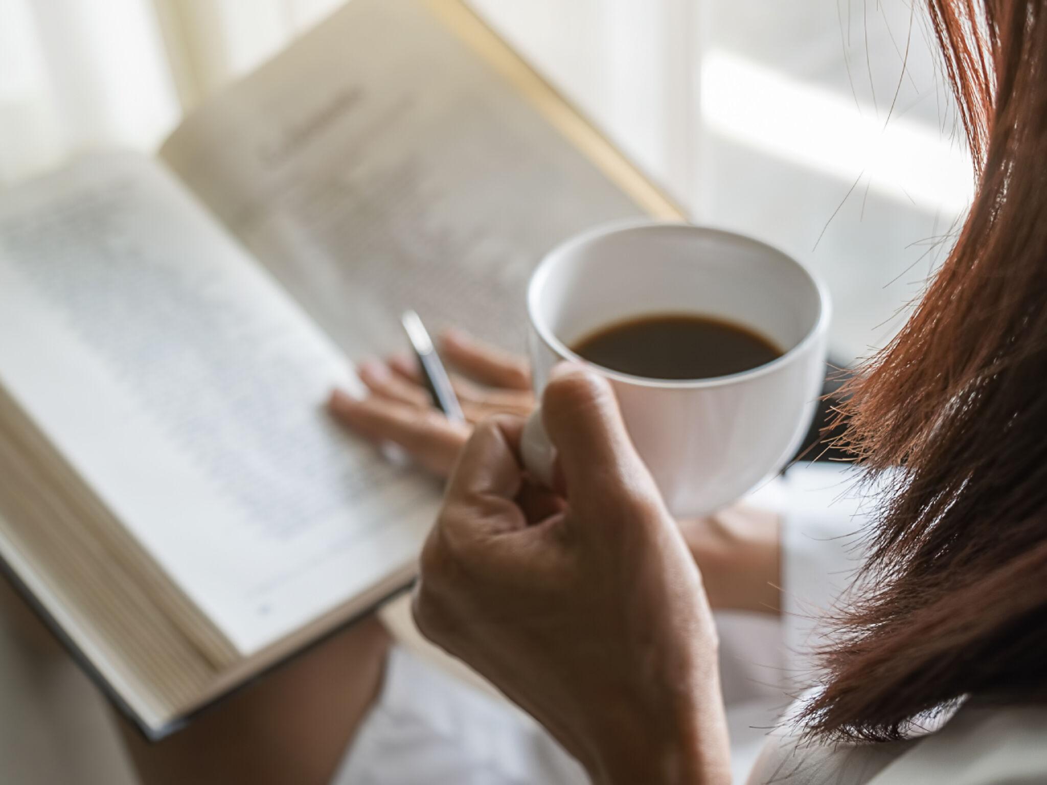 コーヒーを飲みながら読書をしている女性の画像