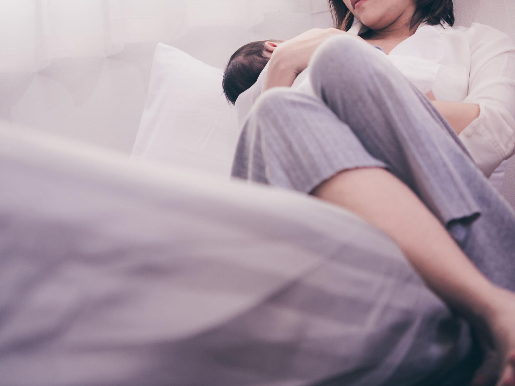 母親が赤ちゃんを抱いてベッドに座っている画像