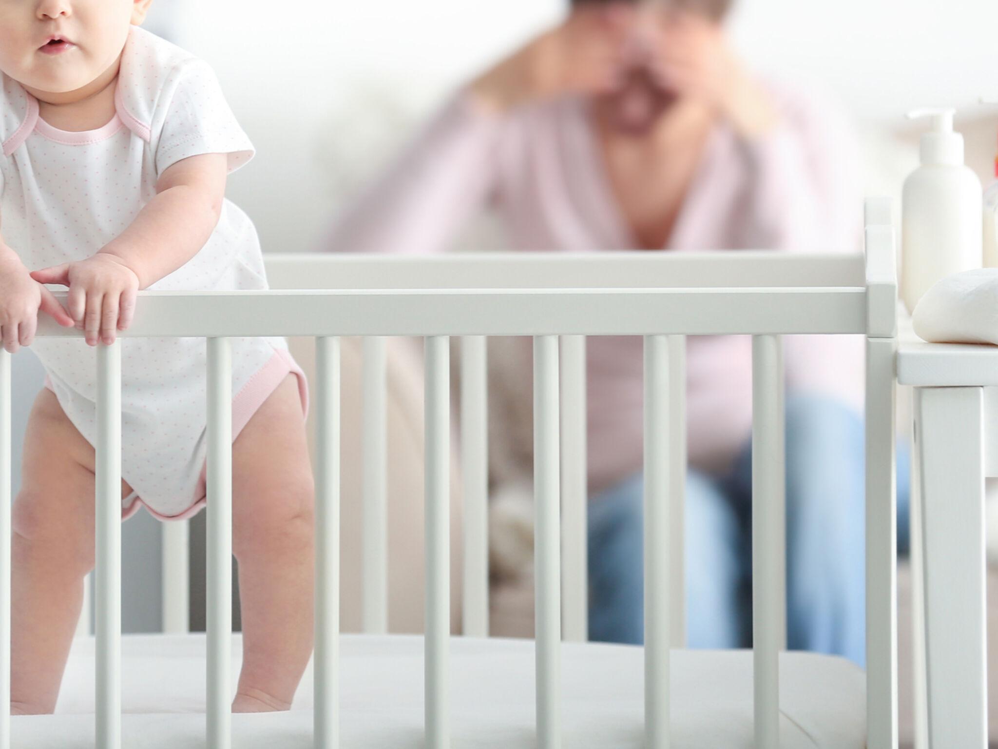 ゲージの中にいる赤ちゃんの前で頭を抱える母親の画像