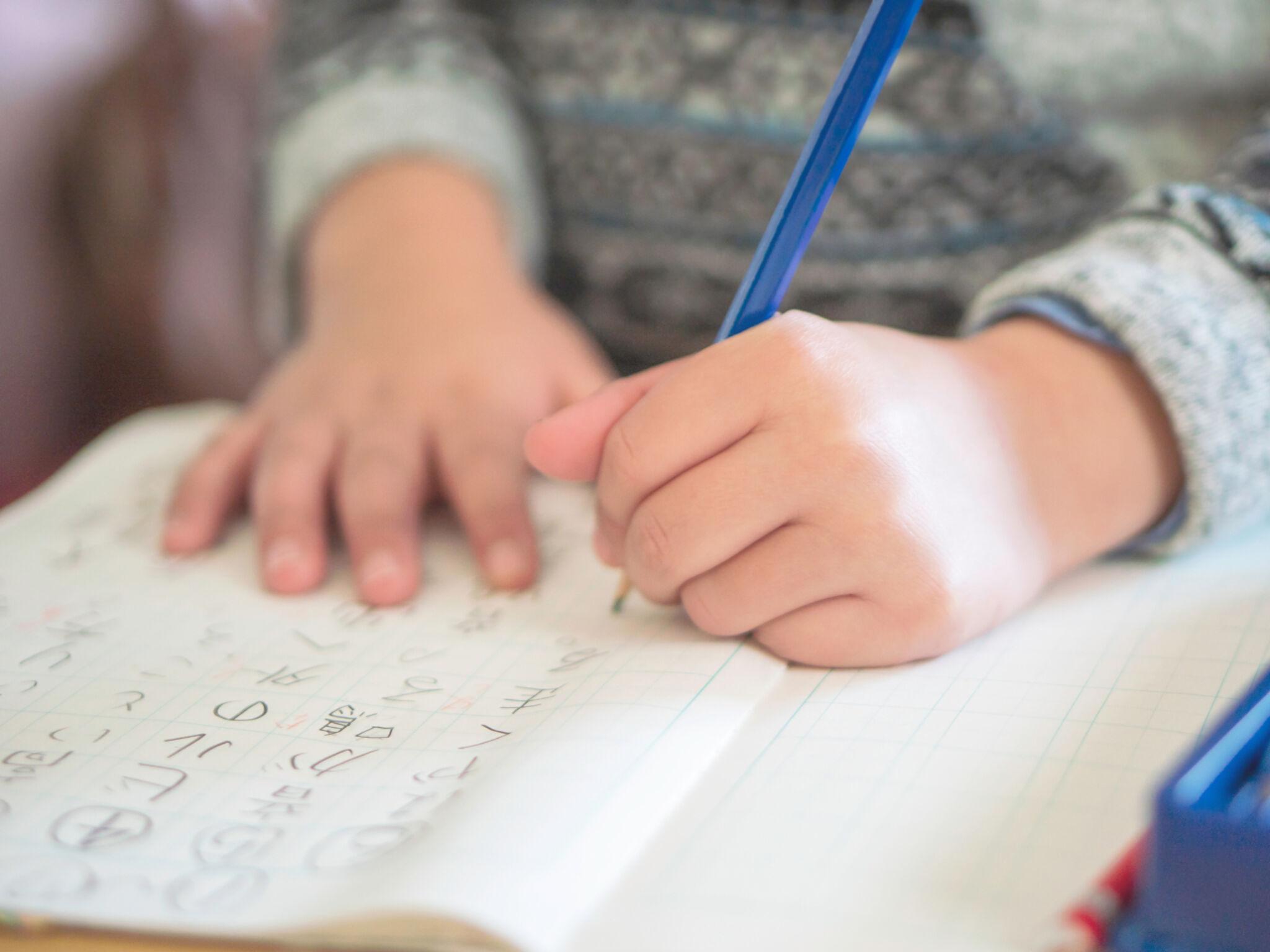 小学生がノートに文字を書いている画像