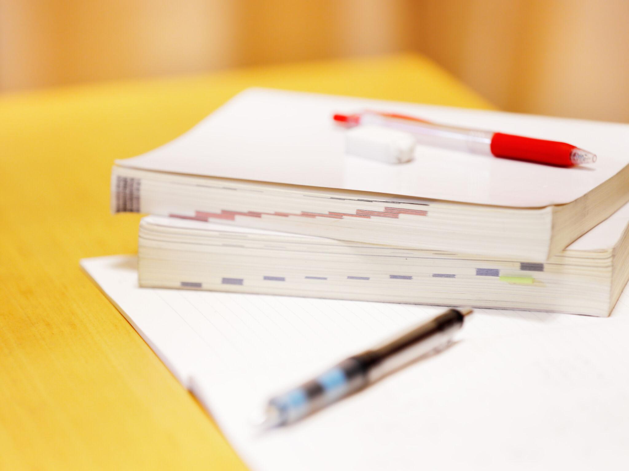 机の上に置かれた教材とペンの画像
