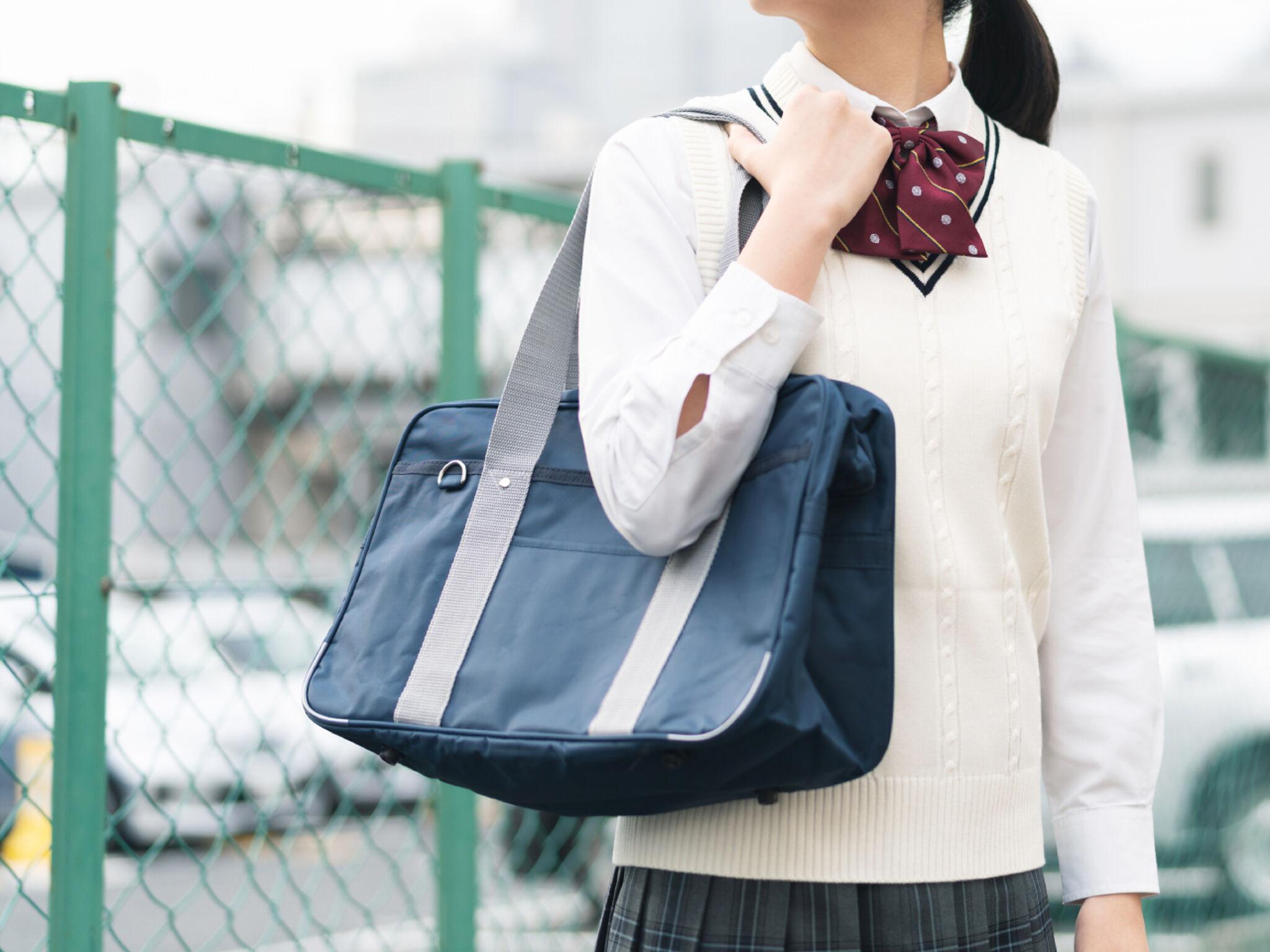 外でバッグを持つ女子高生の画像