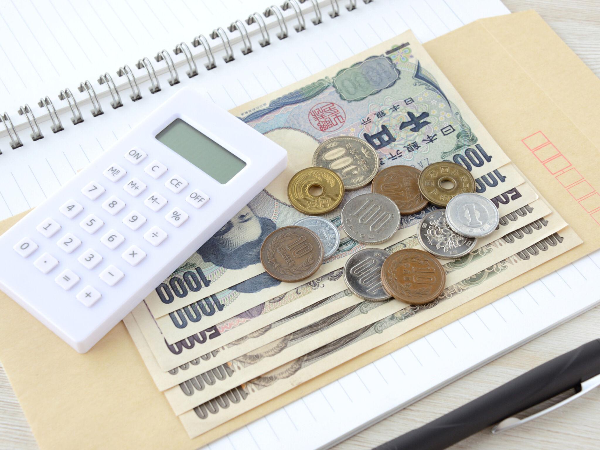 ノートの上に置かれた電卓とお金の画像
