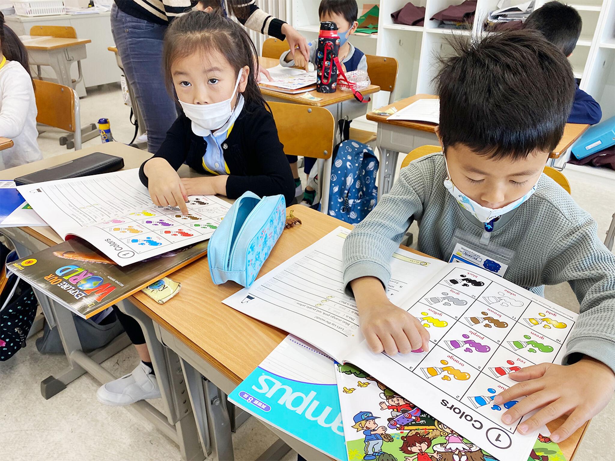 男女2人の子どもが机を並べてテキストを指さし発音の練習をしている様子