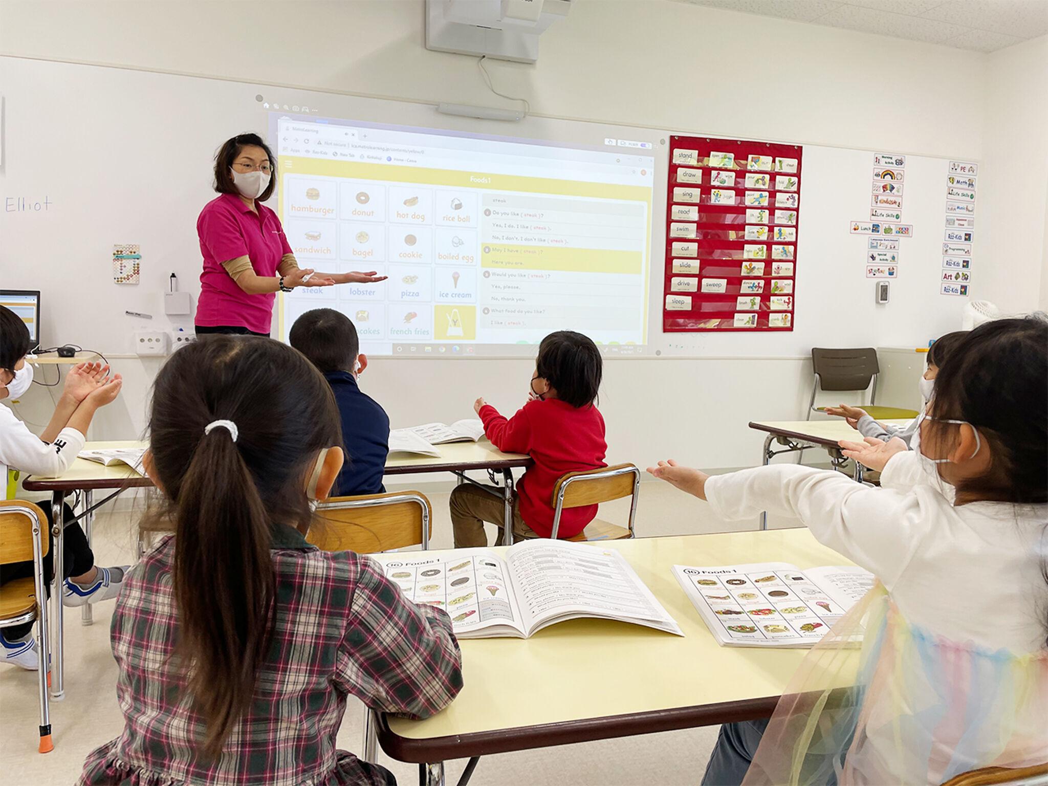 講師と子どもたちが一緒に両手を前に出して英語の発音を練習している様子