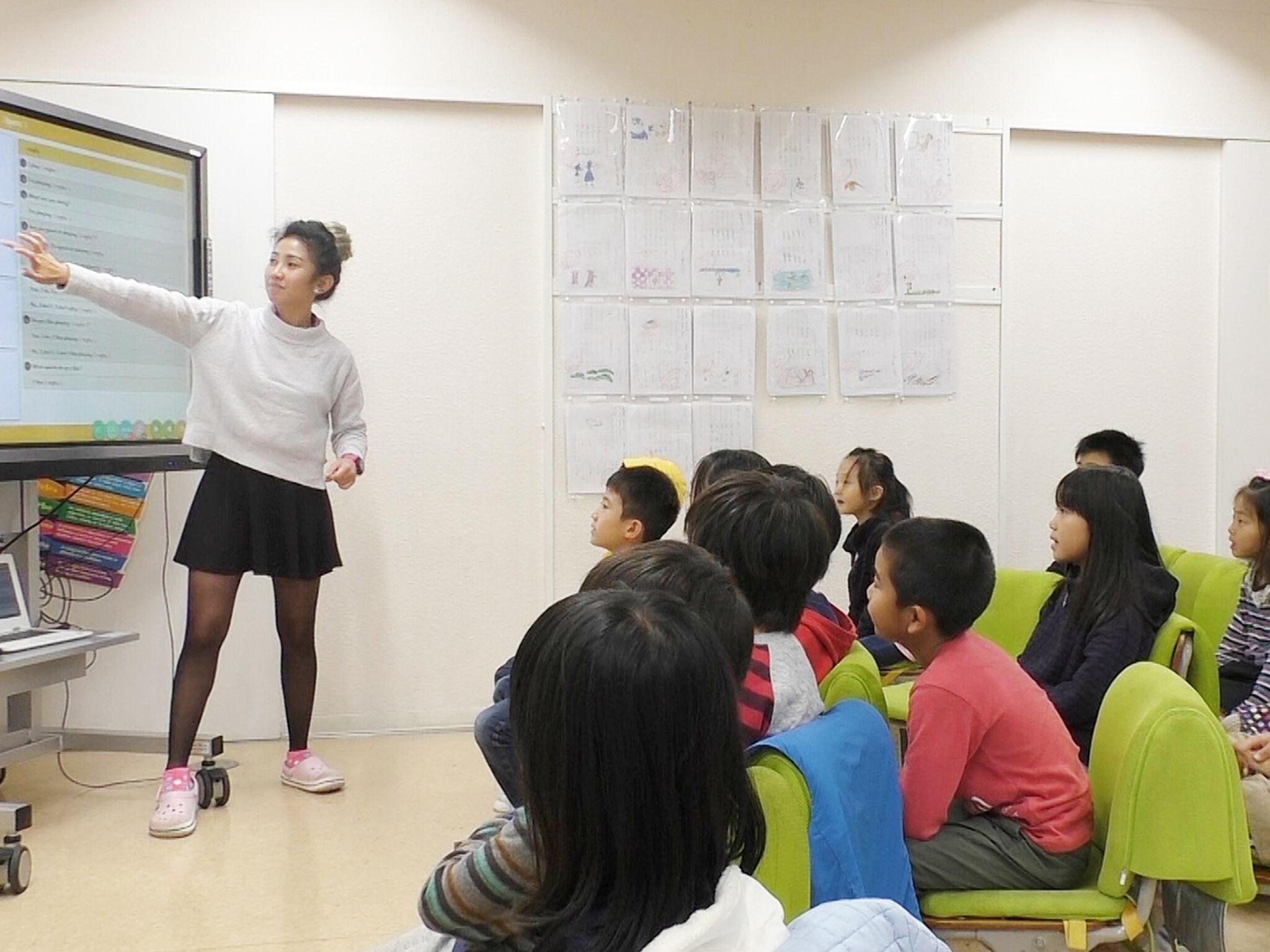 女性のネイティブ講師がスクリーンを指さしながらこどもたちに発音のしかたを教えている様子