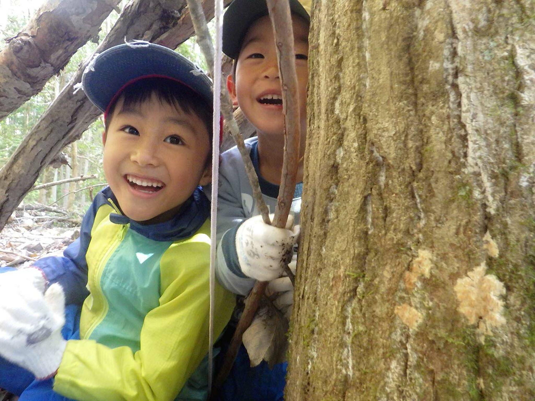 木の横で笑っている子どもの画像