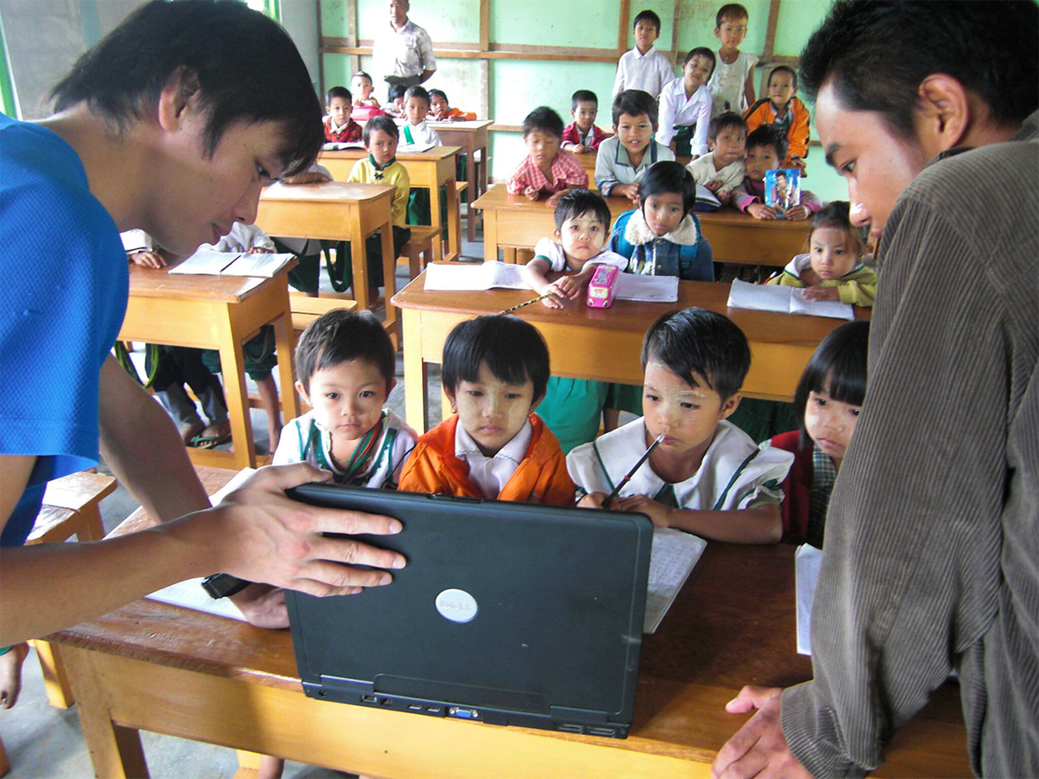 ミャンマーで子どもたちにパソコンを見せている様子の画像
