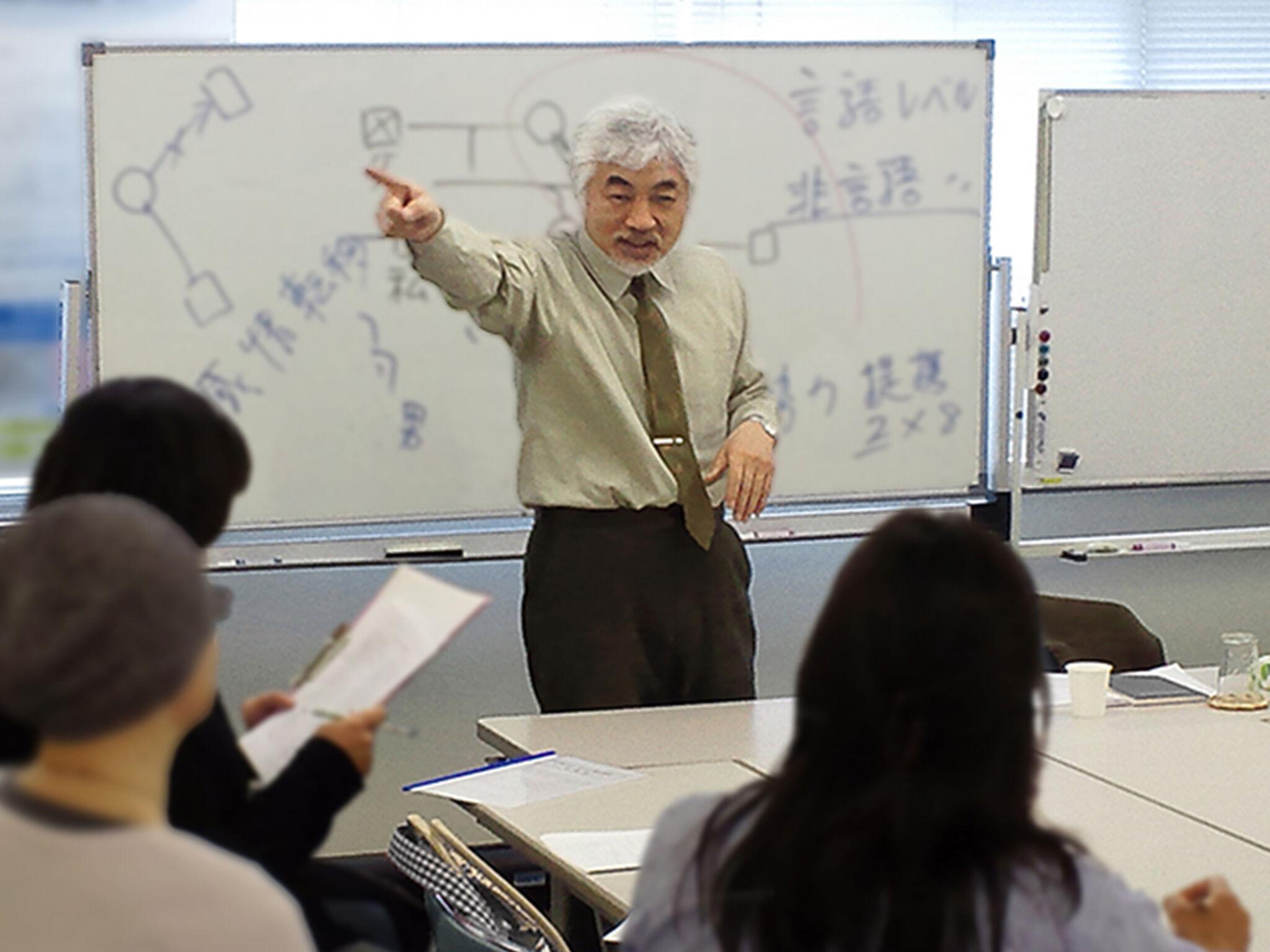 所長がホワイトボードの前で話をしている様子の画像