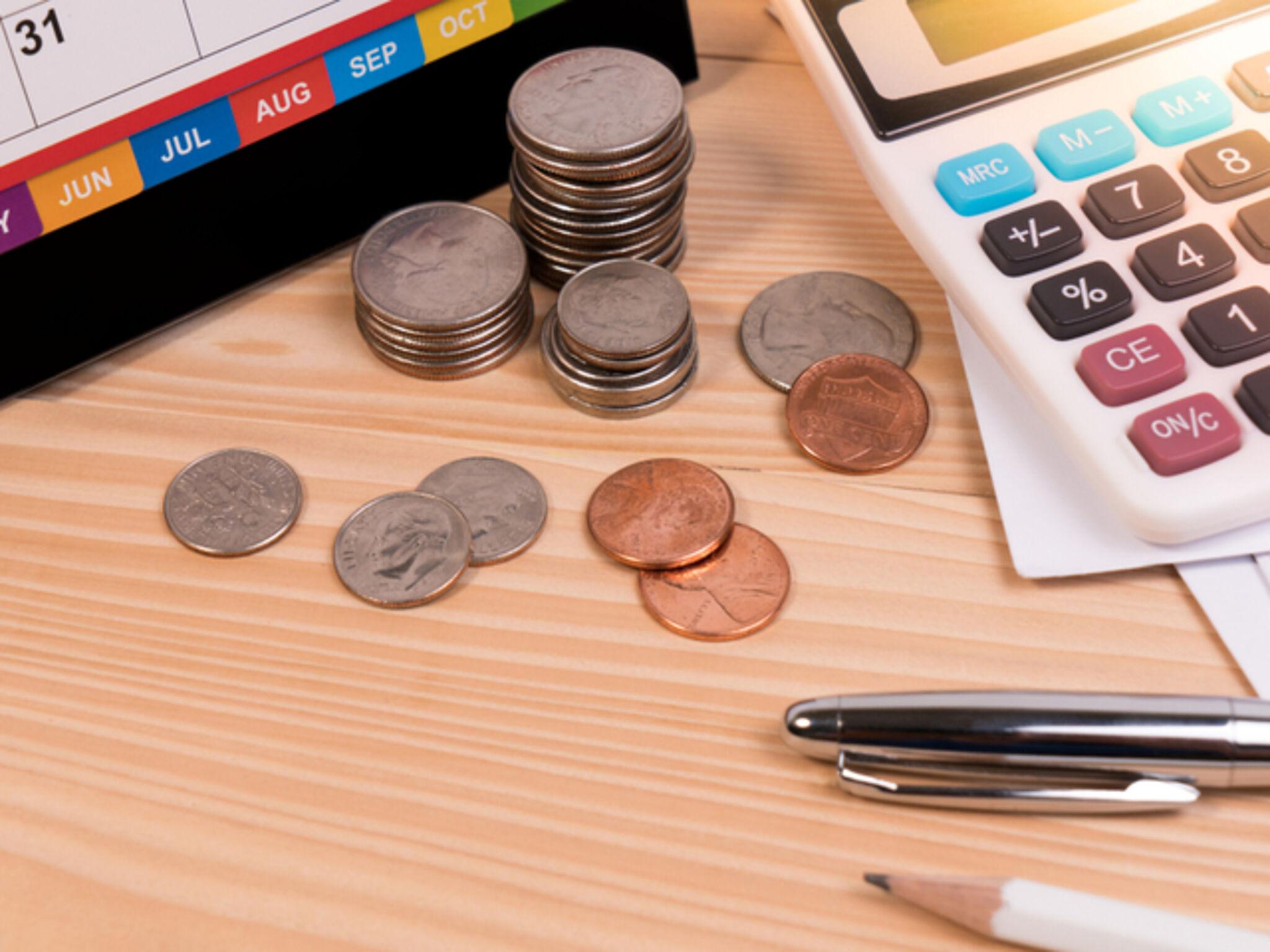 机の上にカレンダーやお金や電卓機などが置いてある画像