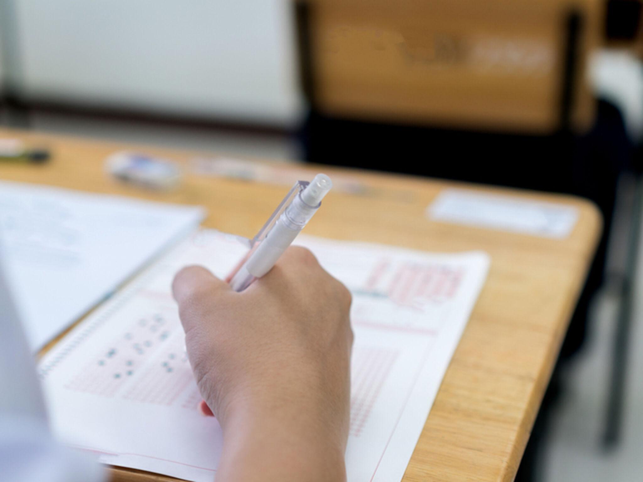 問題を解いている高校生の手のアップの画像