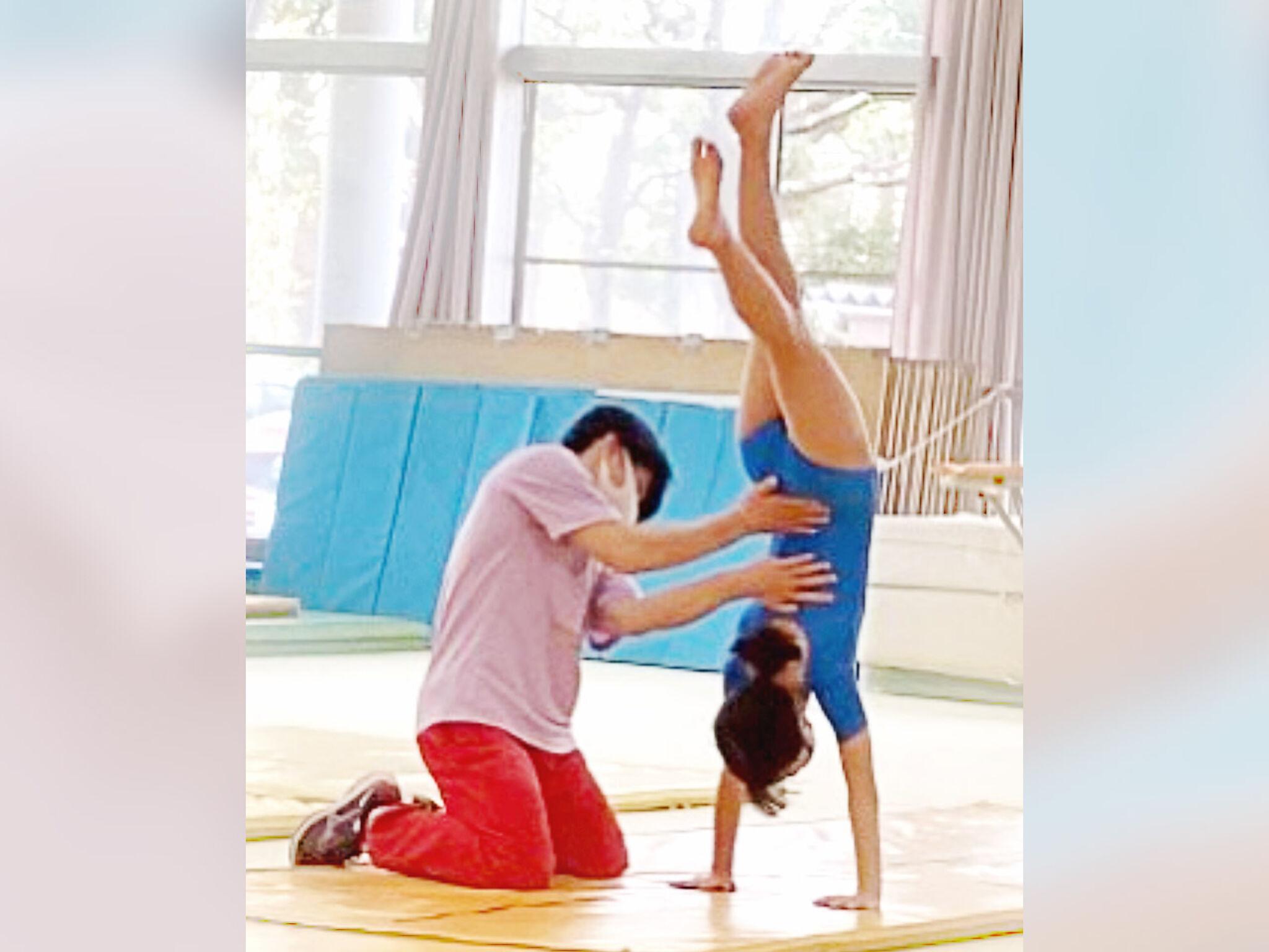 体操教室で子どもが逆立ちしている画像