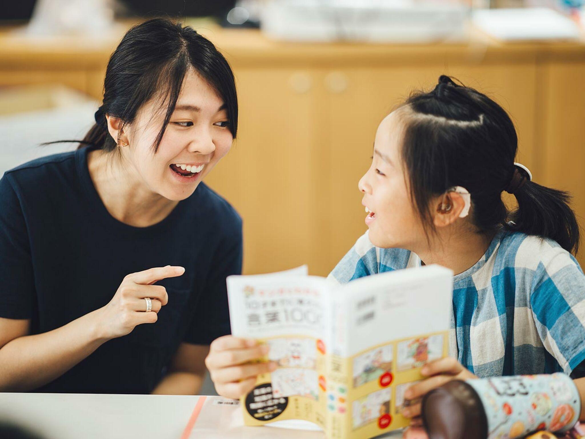 子どもと女性スタッフが一緒に本を見ている画像