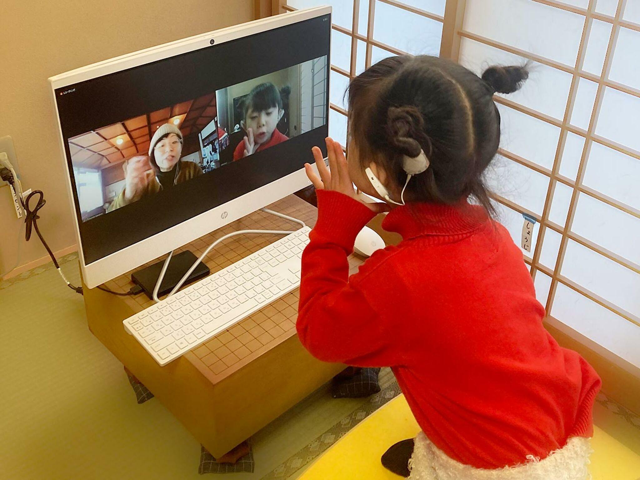 女の子がパソコンに向かって会話をしている画像