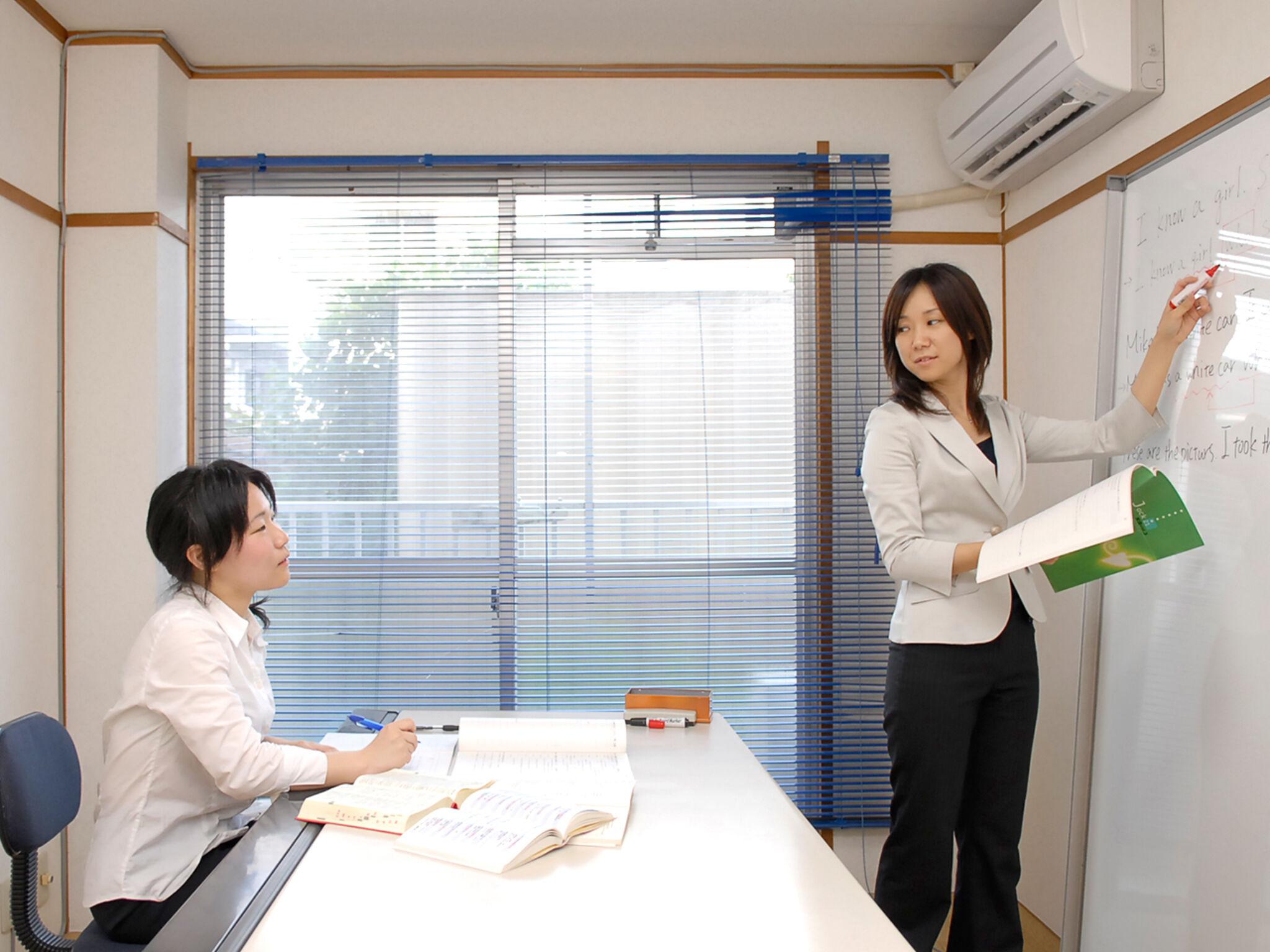 生徒が女性の講師に指導を受けている画像