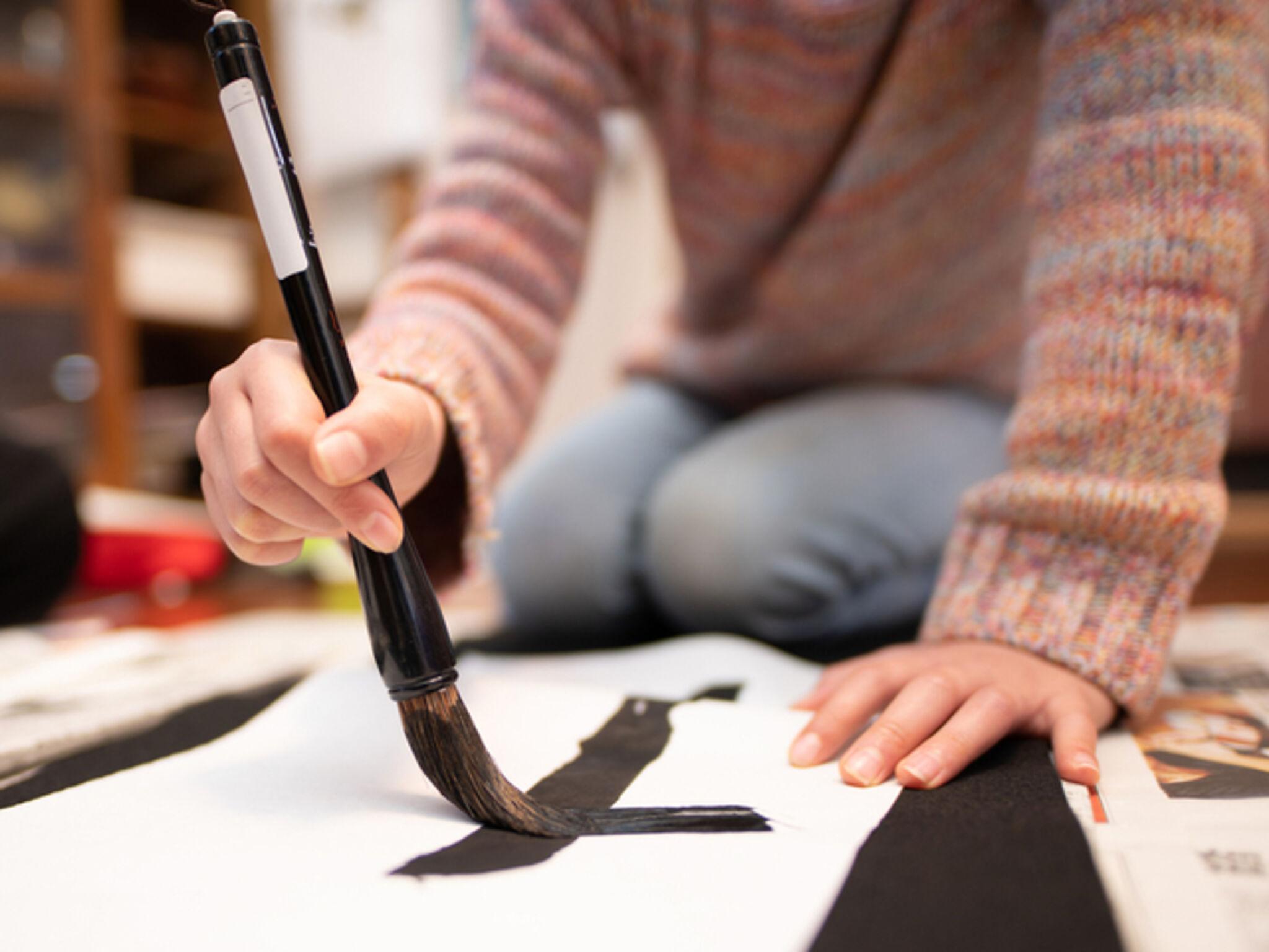 毛筆を練習している子どもの画像
