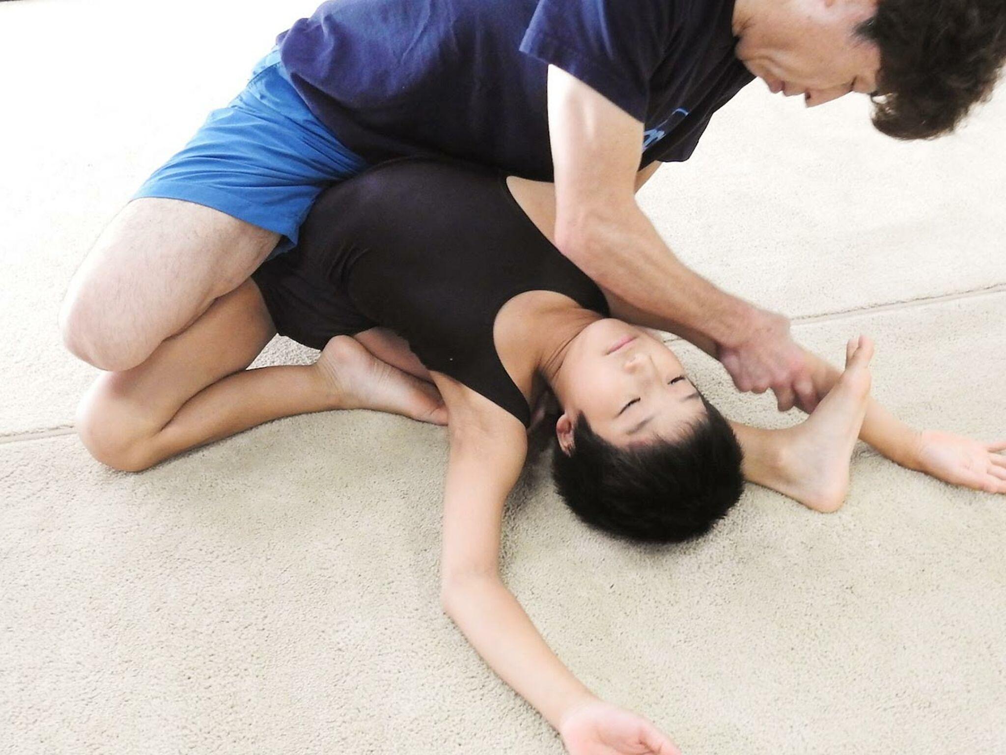 先生が男の子にストレッチの補助をしている画像