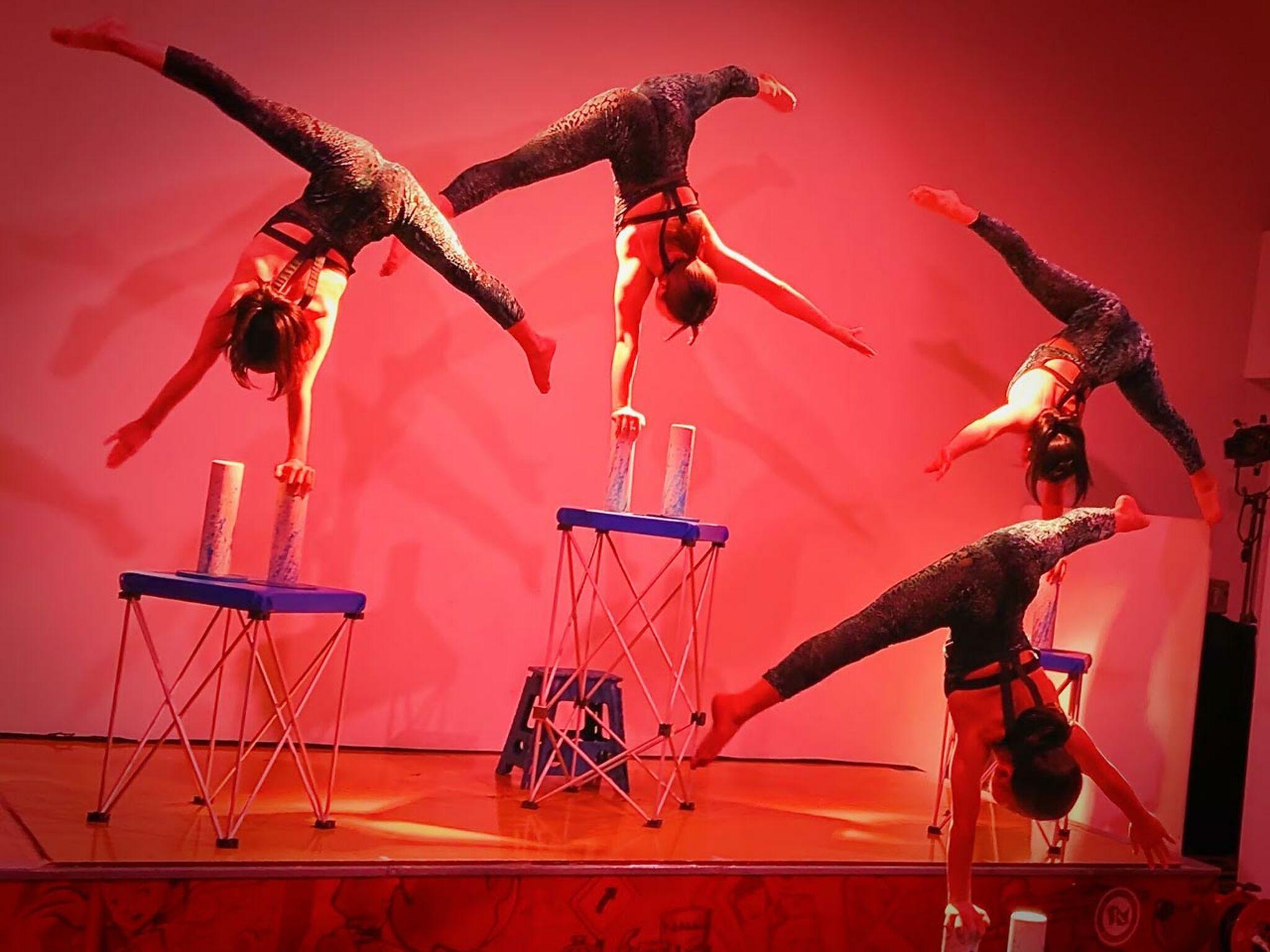 赤い照明の中、体操のショーをおこなっている画像