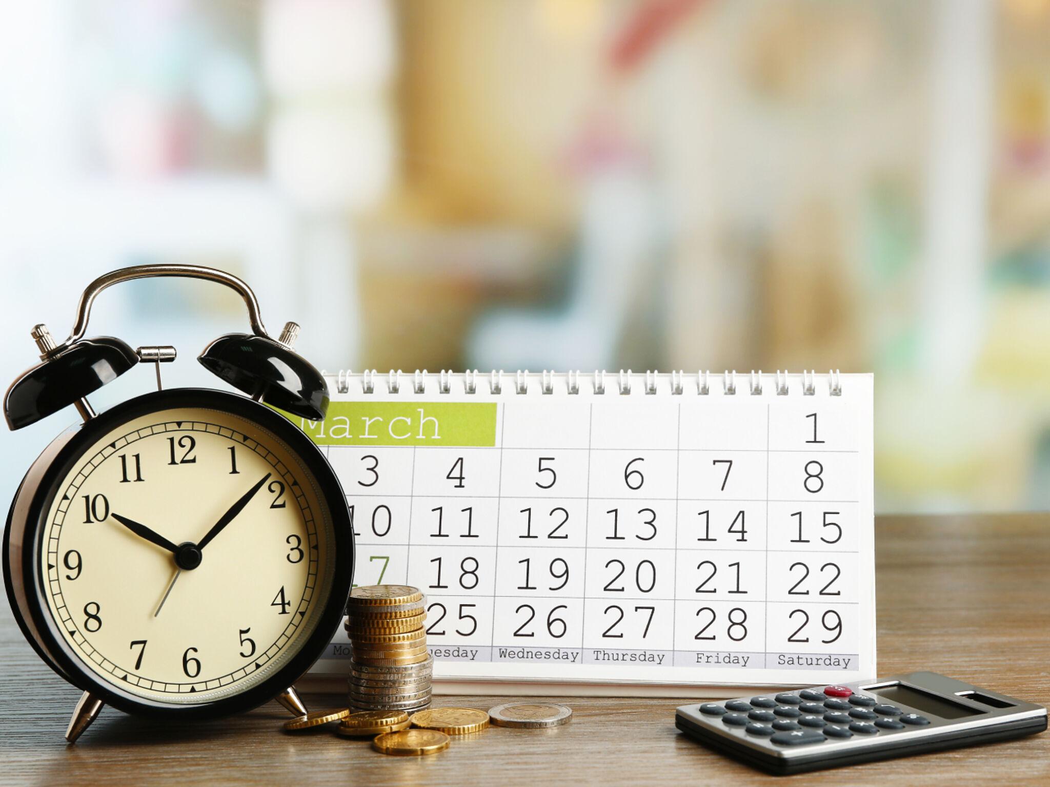 机に置いてある時計とカレンダー、計算機、お金の画像