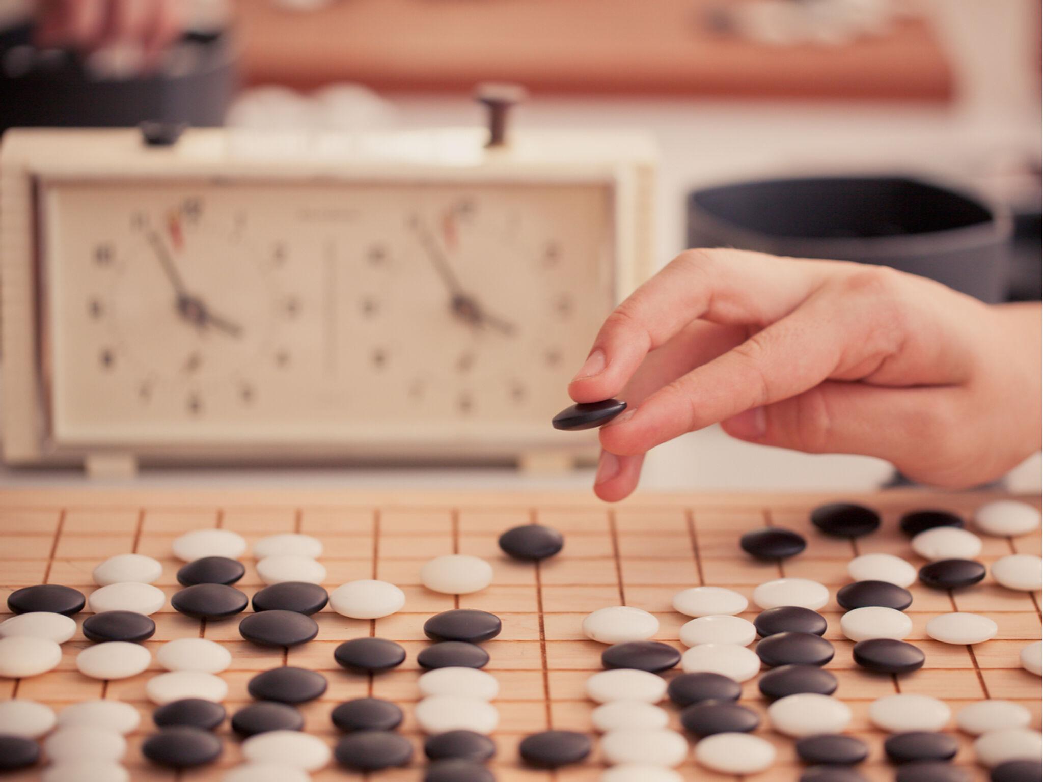将棋をさす手と時計がうつっている画像