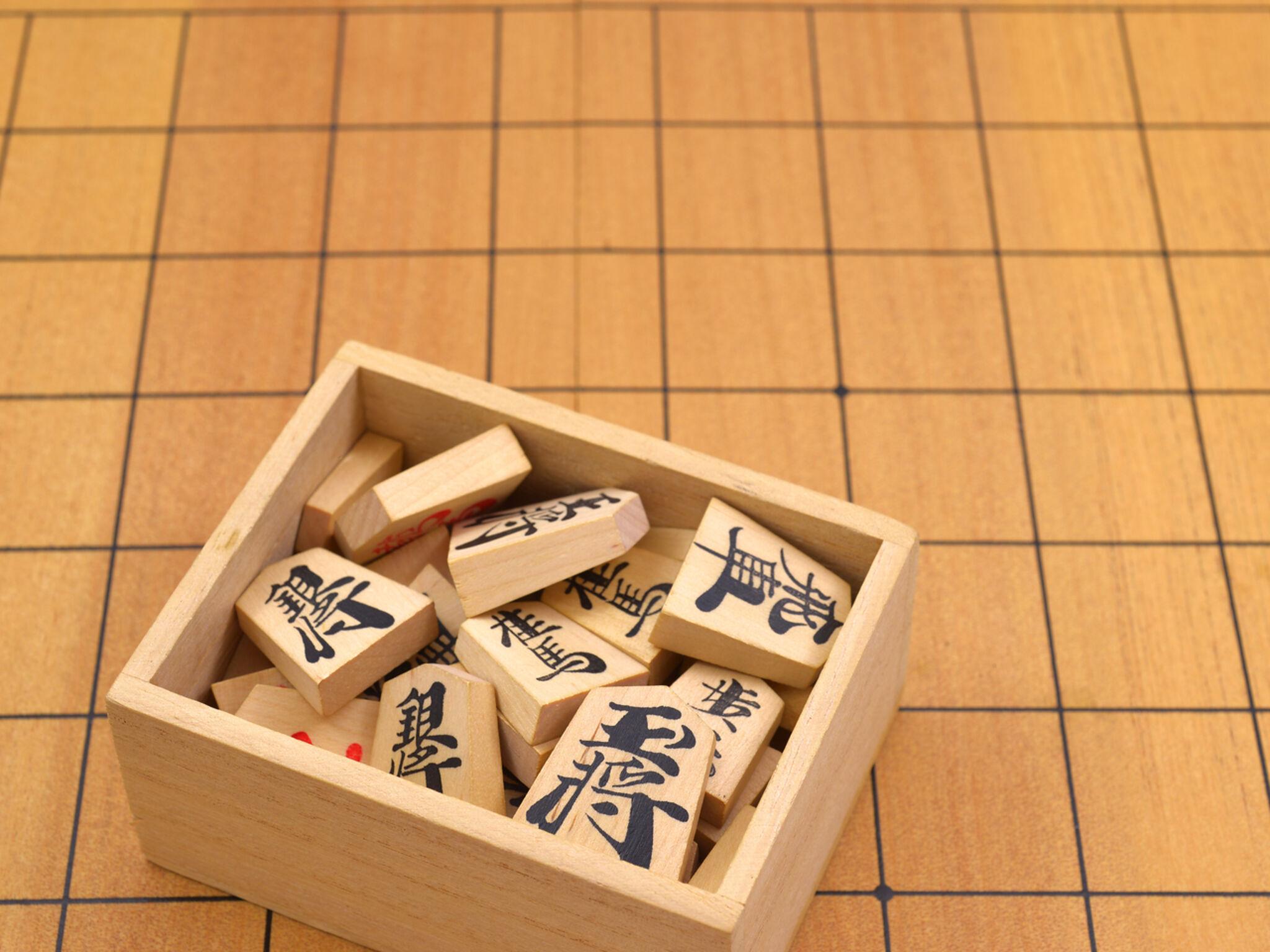 将棋盤の上に駒とケースが置いてある画像