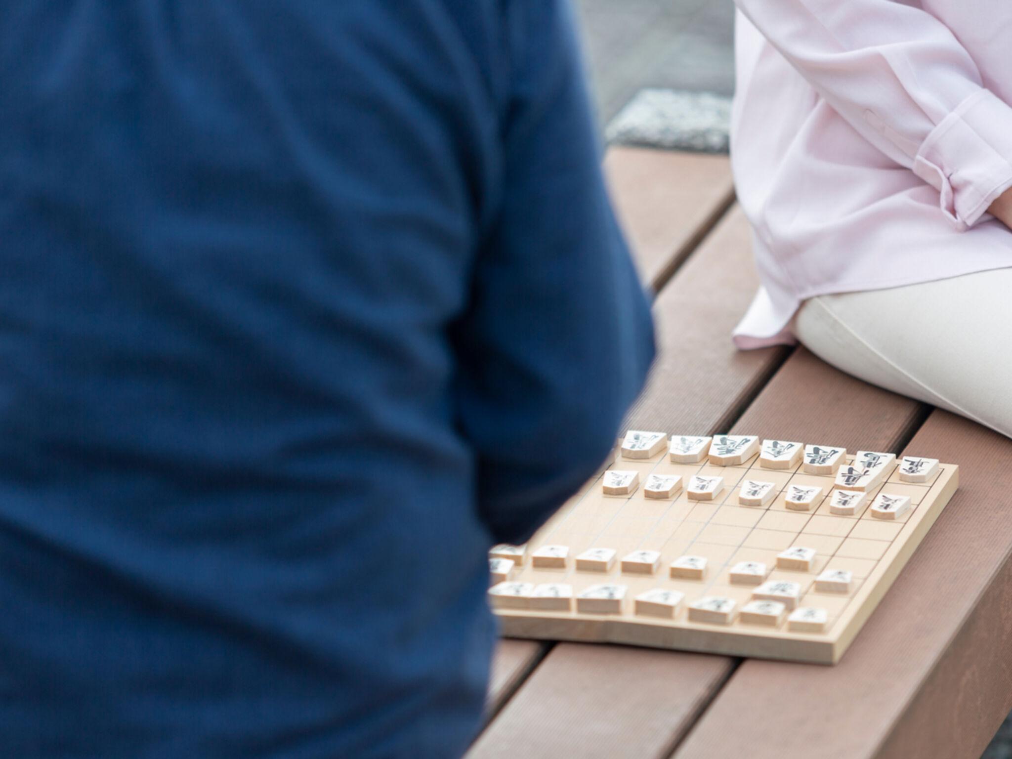 大人2人がベンチに座って将棋をさしている画像