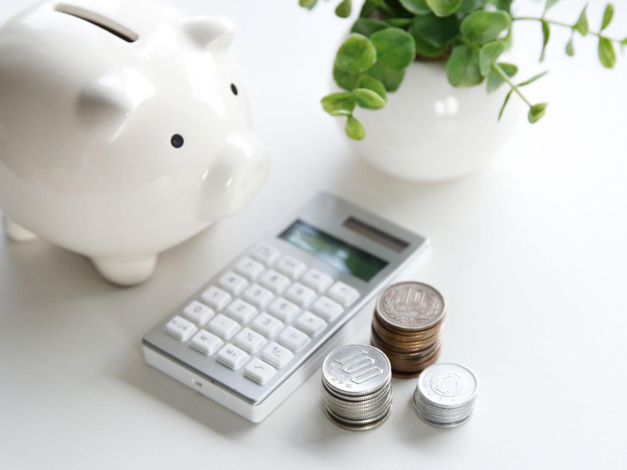 貯金箱と計算機と小銭の画像