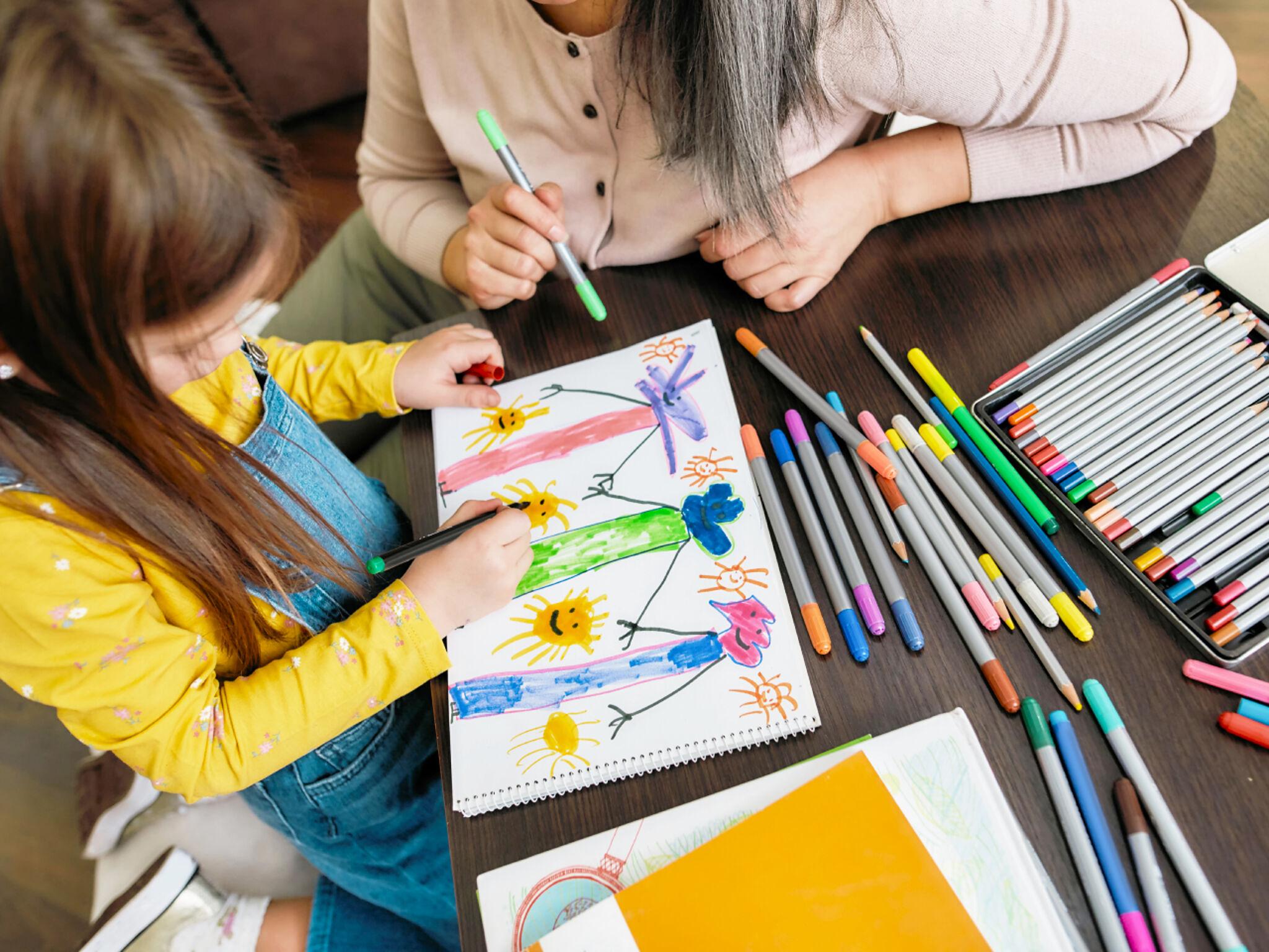 絵を教える先生と子どもの画像