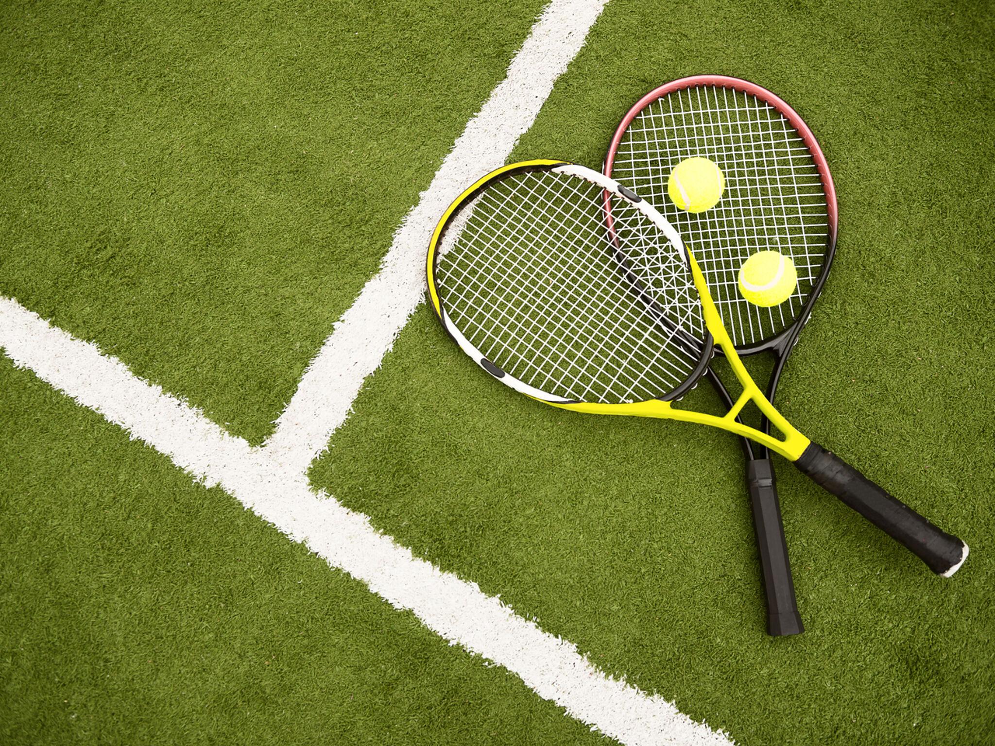 緑の芝生にラケットとボールが2つずつ置いてある画像