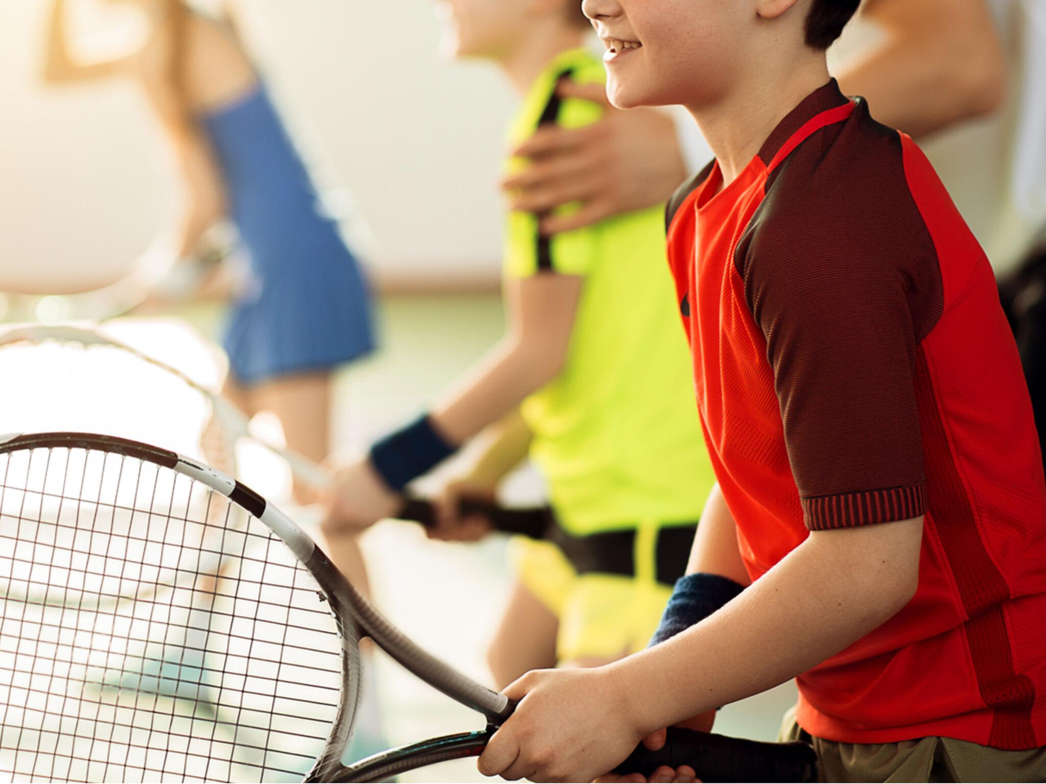 子ども3人がテニスの指導を受けている画像