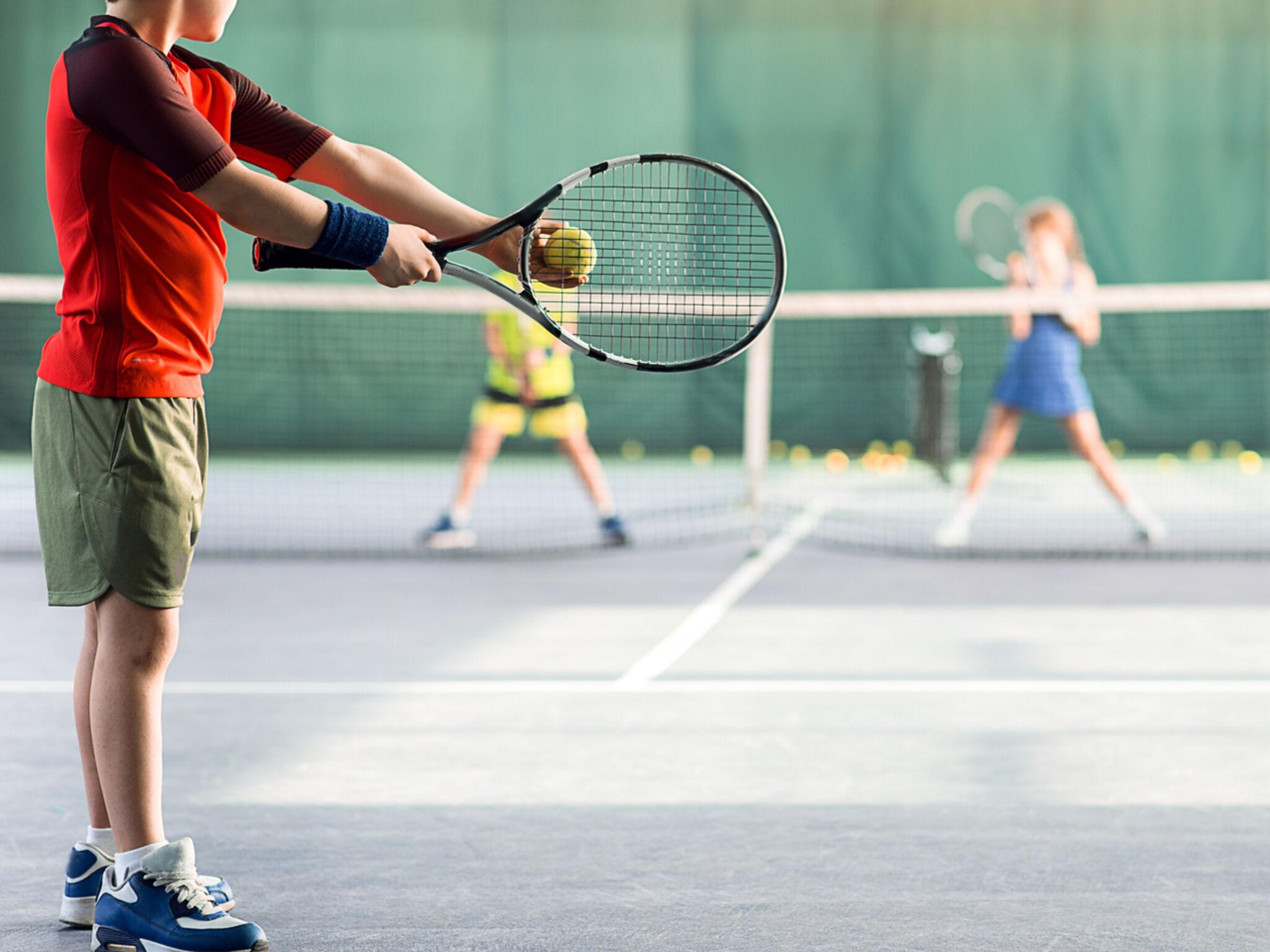 子ども3人がテニスをしている画像