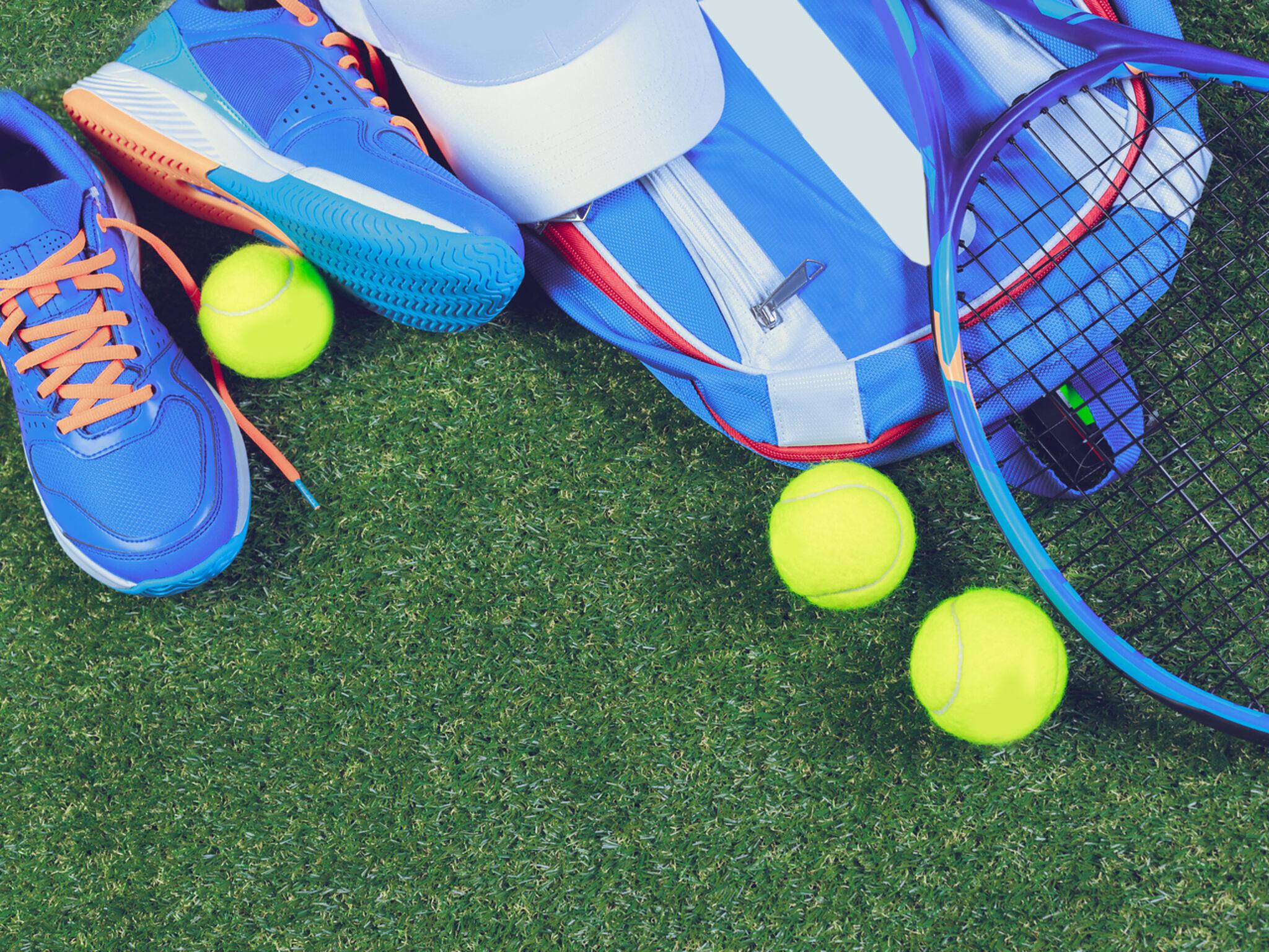 コートの上にラケットやボール、リュックなどが置いてある画像