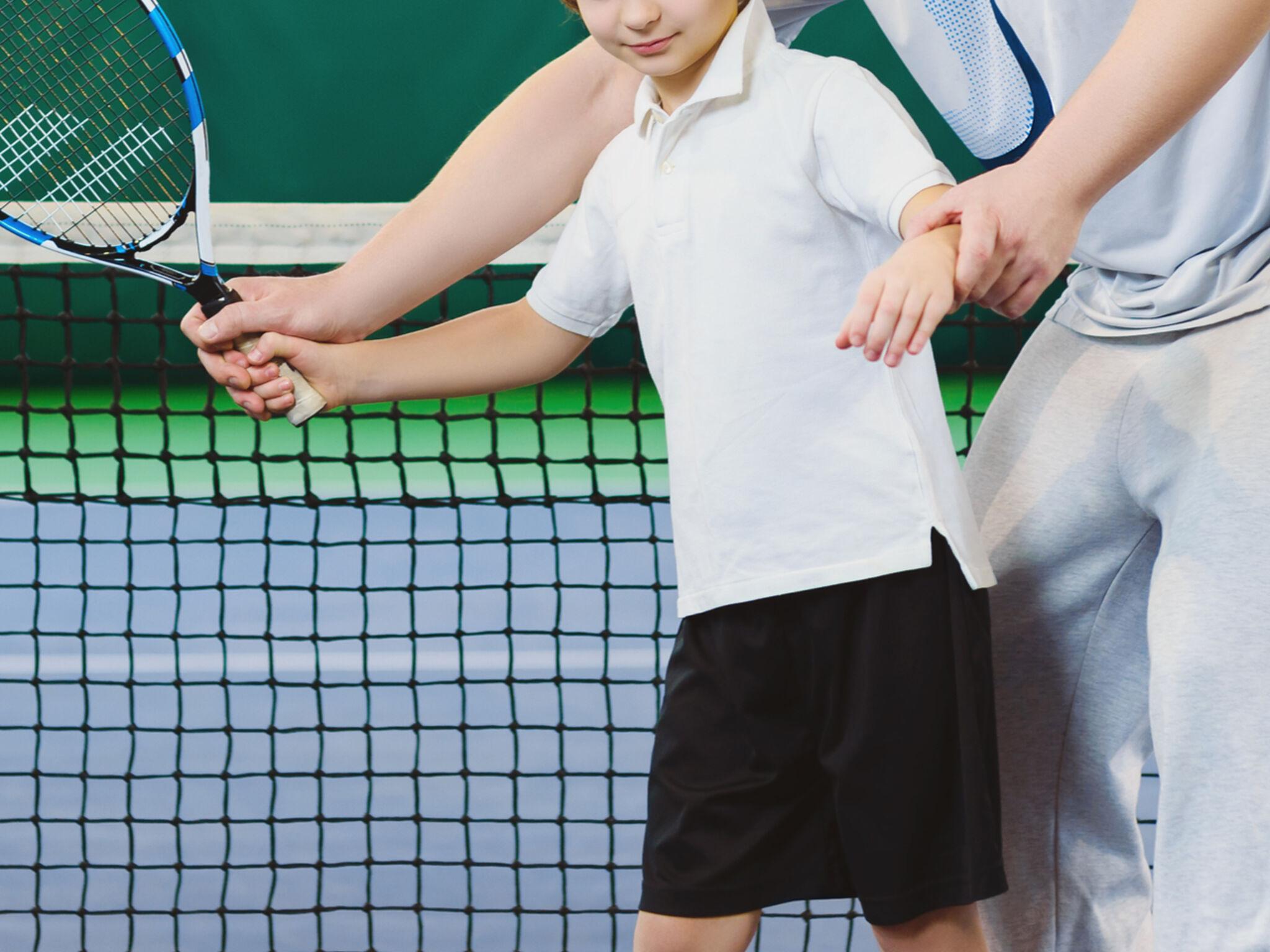 男の子がコーチにテニスの指導を受けている画像