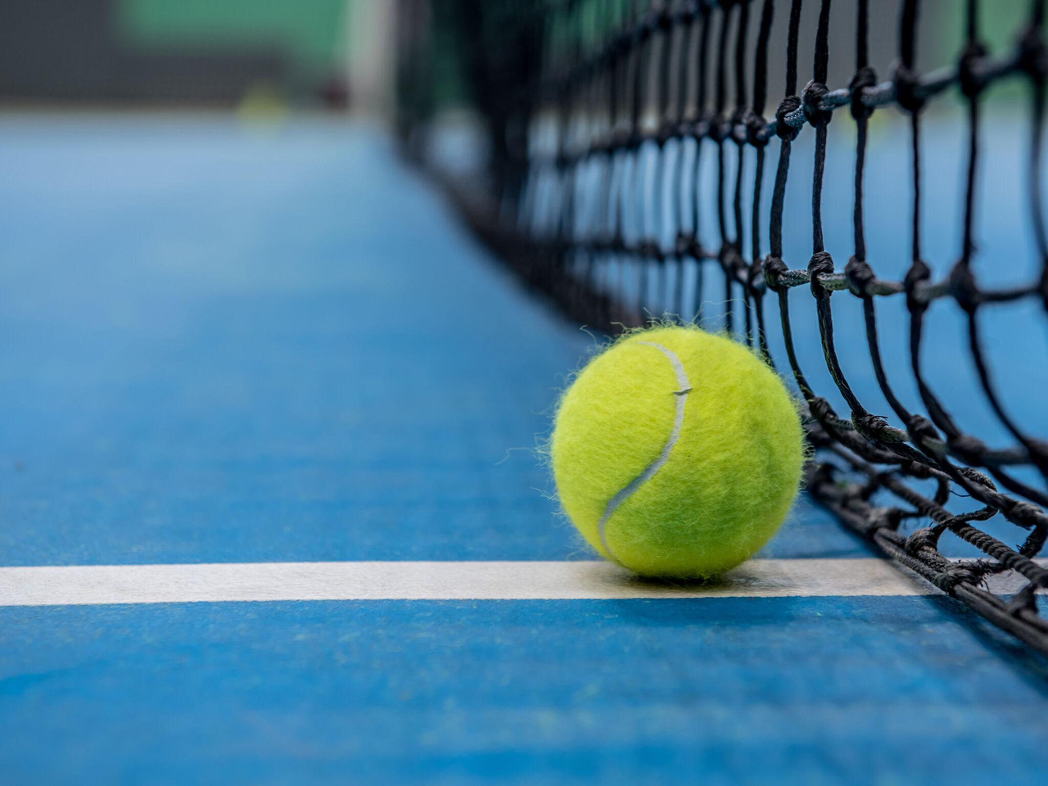青いテニスコートにボールがひとつ置いてある画像
