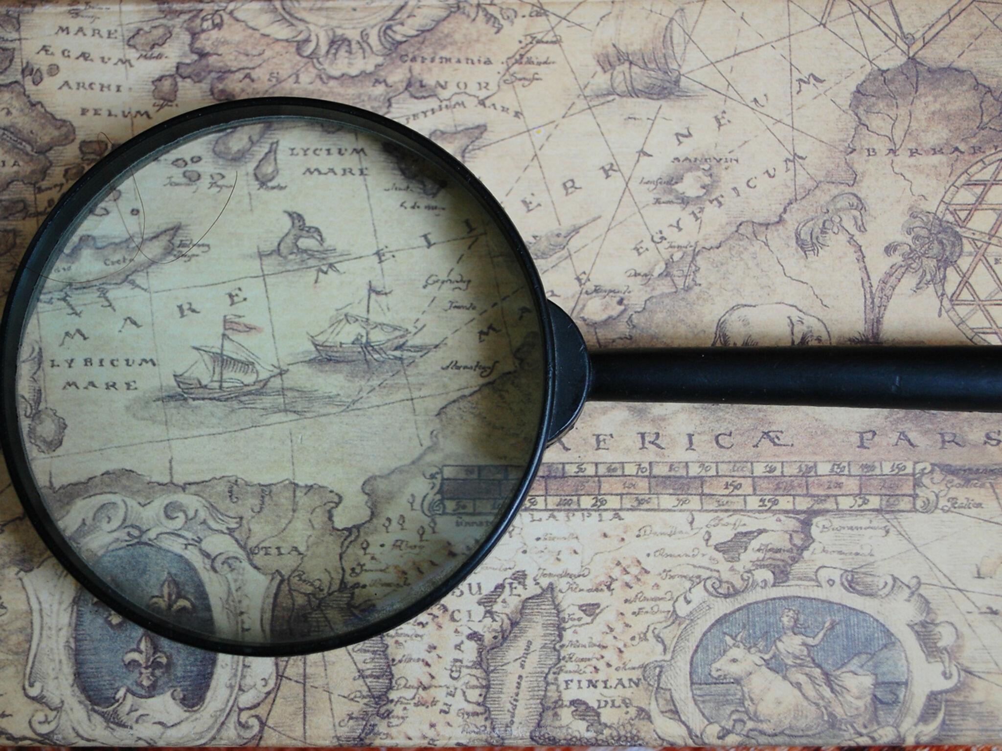昔の世界地図に虫眼鏡が置いてある画像