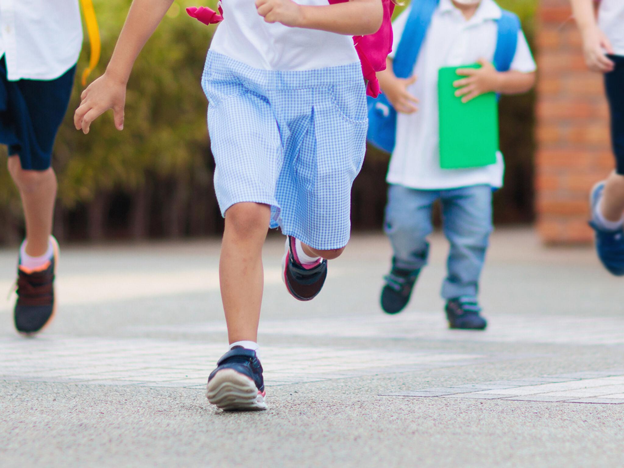 子ども4人が学校帰りに走っている画像
