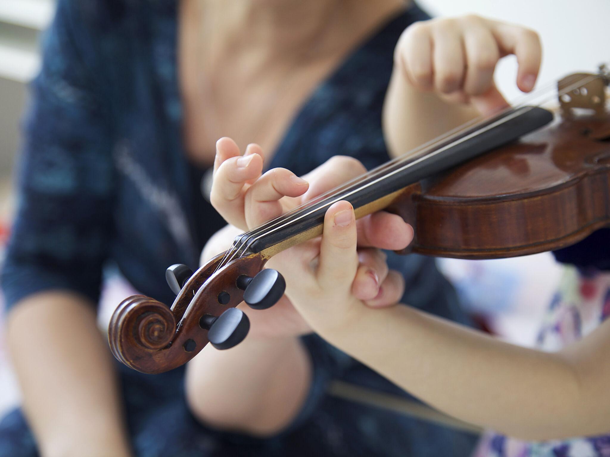 子どもが女性の先生にヴァイオリンを直接指導してもらっている画像
