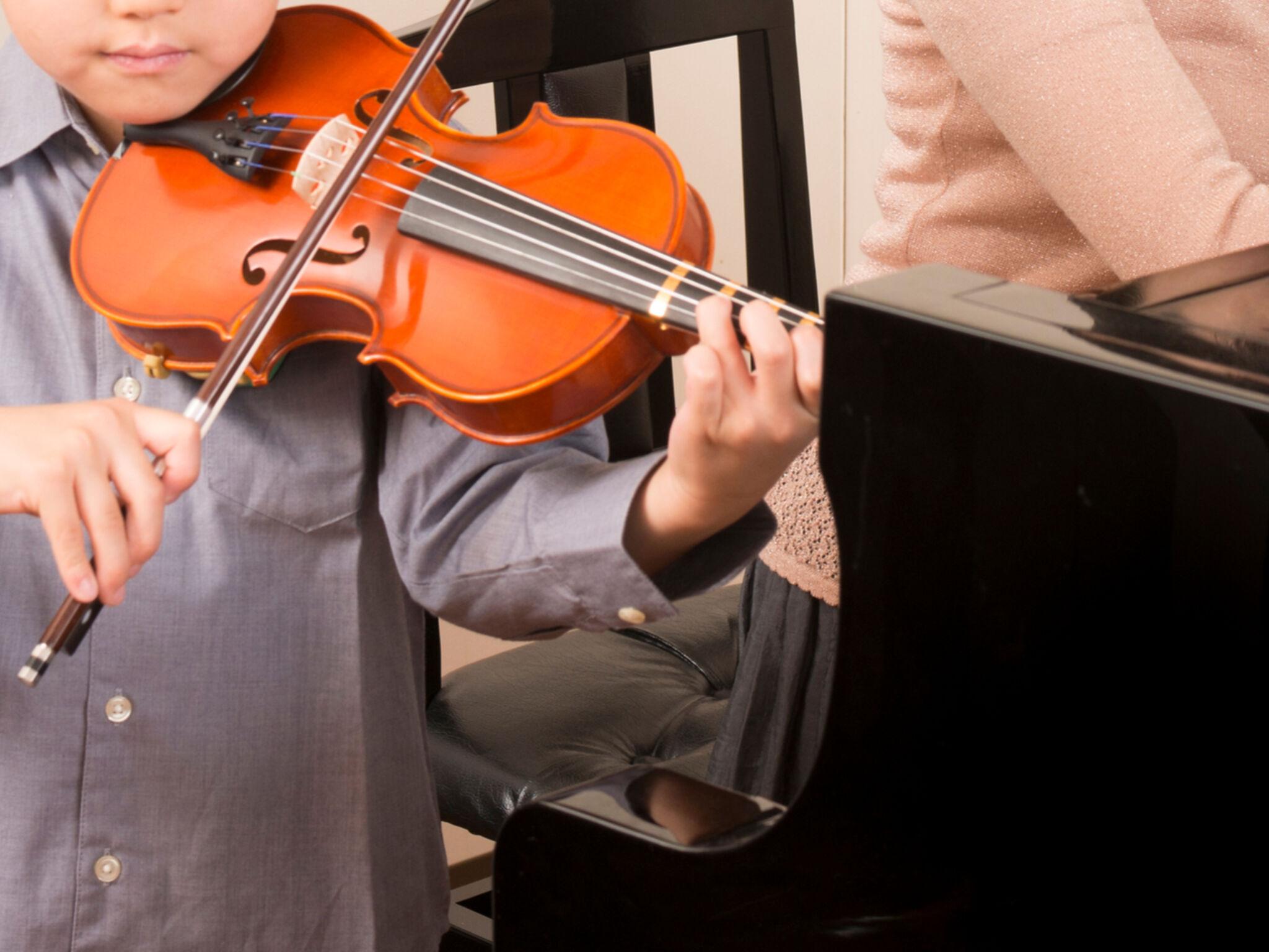 ピアノをひいている先生に合わせて子どもがヴァイオリンを弾いている画像