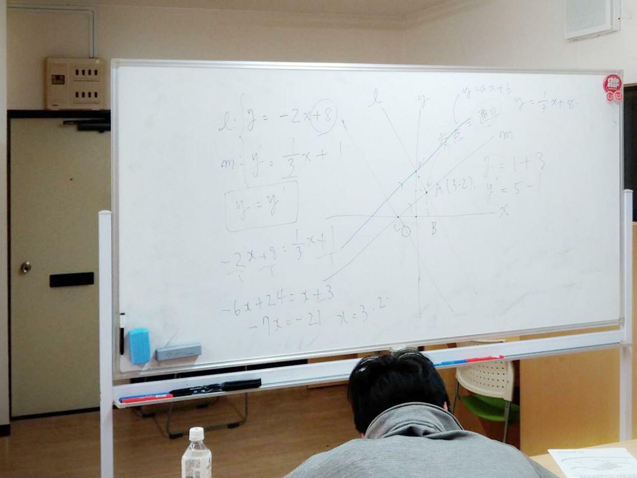 ホワイトボードを見て生徒が勉強している画像