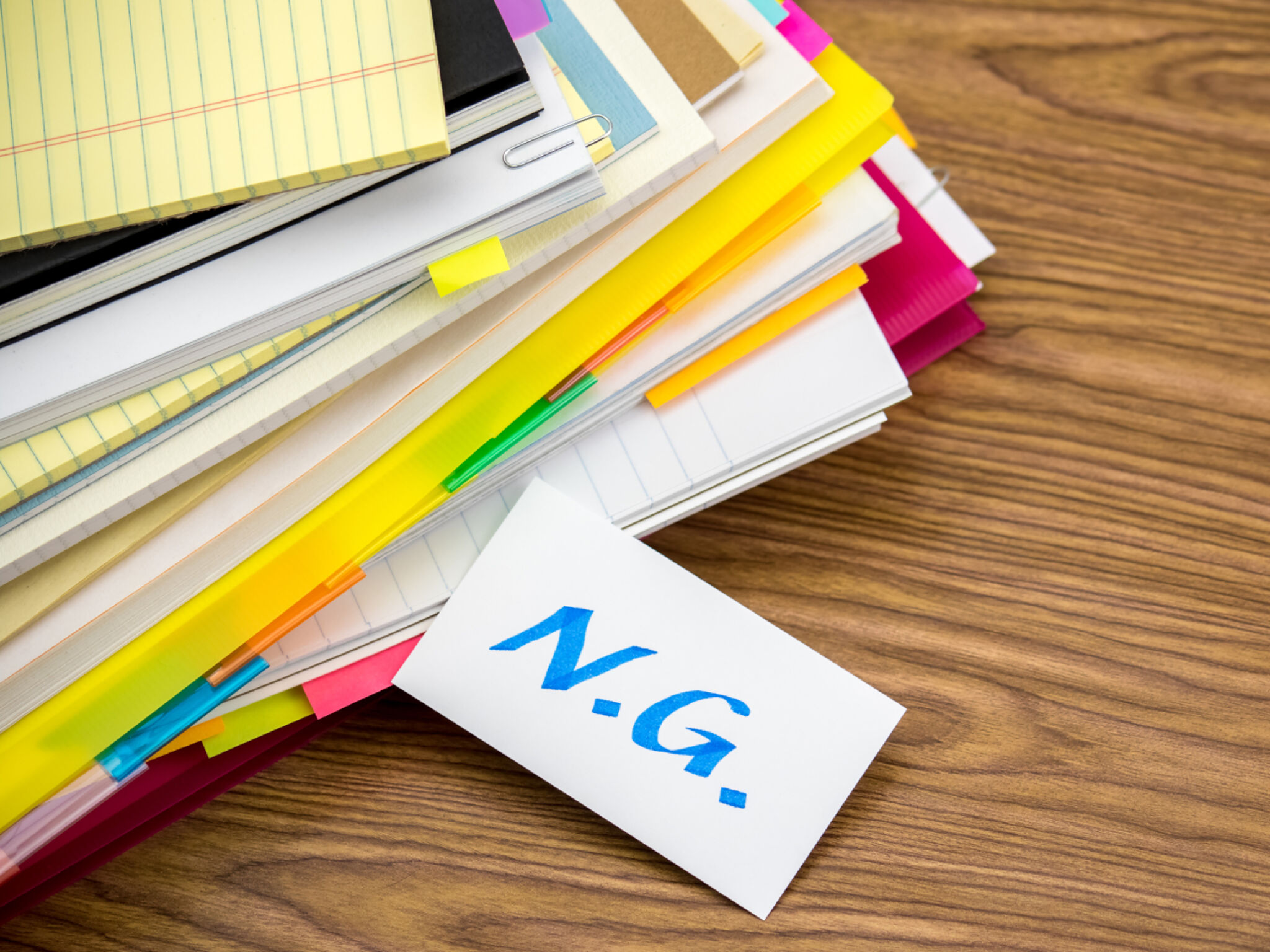 積み重ねられたノートと「NG」と書いてある紙の画像